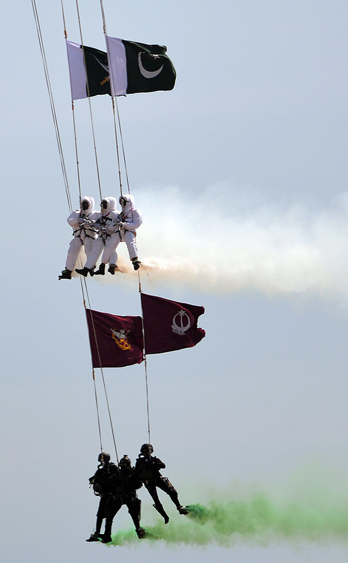 Pakistani commandos hang from a helicopter