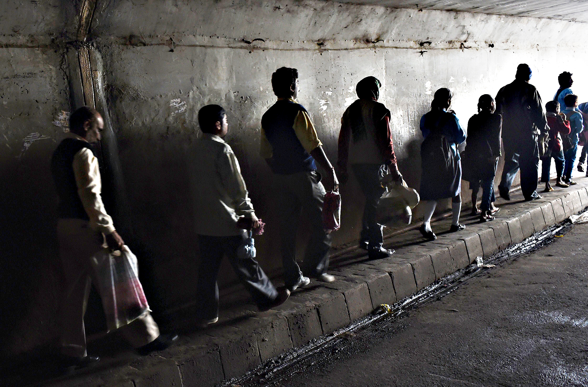 Indian commuters walk in an underpass connecting their neighborhood with a main thoroughfare past a train station in the early hours of the morning in New Delhi on March 10, 2015.  According to a report from the United Nations India's urban population numbers some 410 million people and this will grow to 814 million by 2050. The report from 2014 also states that India is projected to add the highest number of people to its urban population by 2050, ahead of China