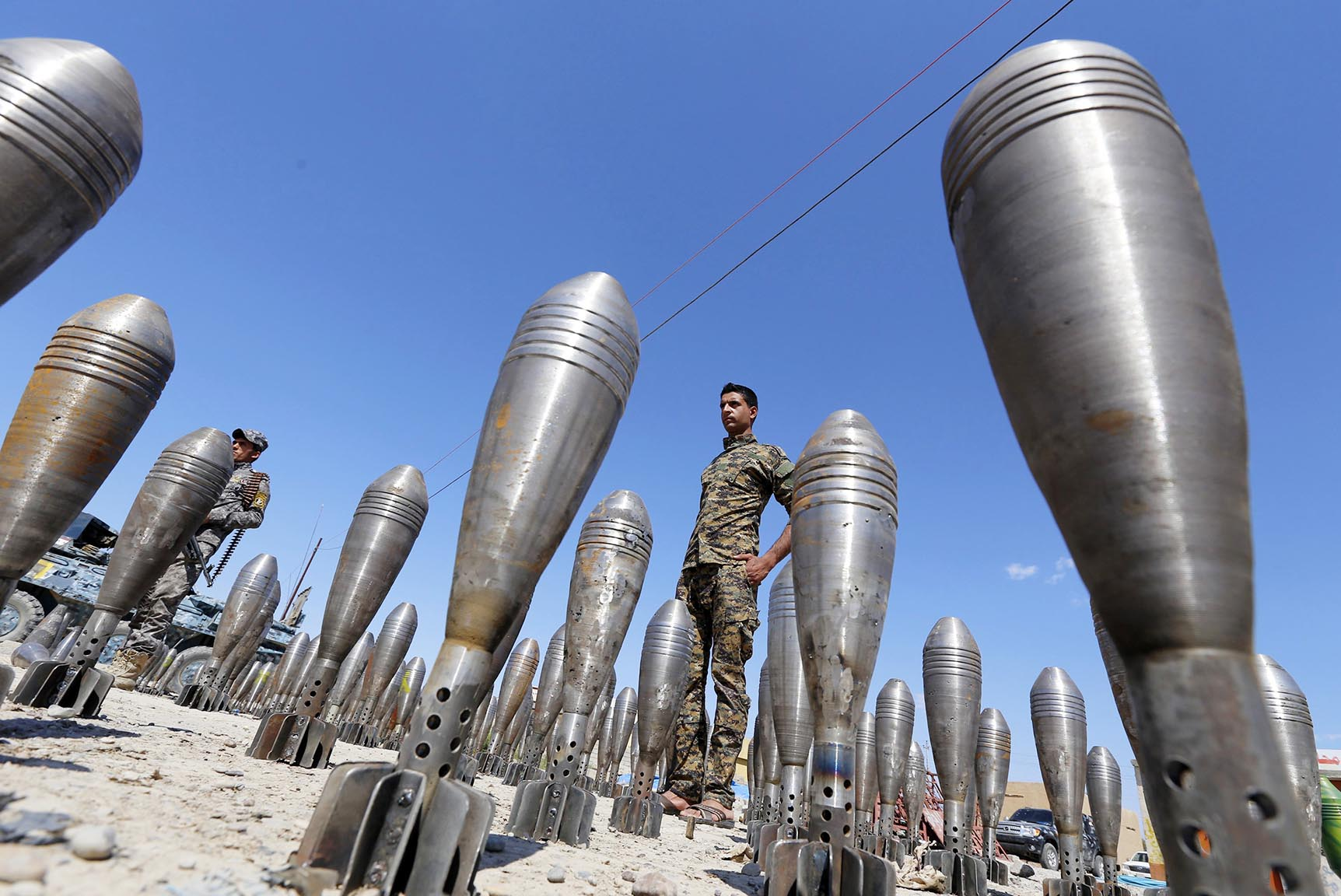 A member of the Iraqi security forces stands between Islamic State ammunition being displayed in al-Alam Salahuddin province