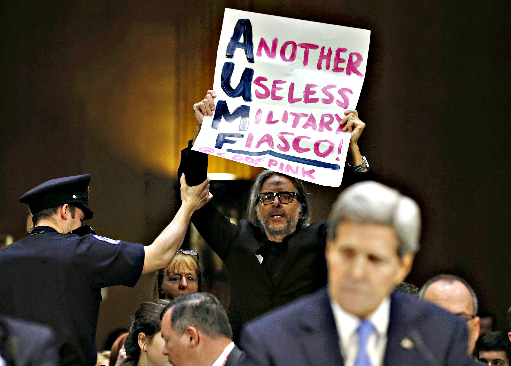 "Police remove a protester holding a sign as U.S. Secretary of State John Kerry testifies at a Senate Foreign Relations Committee hearing on Capitol Hill in Washington...Police remove a protester holding a sign as U.S. Secretary of State John Kerry testifies at a Senate Foreign Relations Committee hearing on ""The President's Request for Authorization to Use Force Against ISIS: Military and Diplomatic Efforts"" on Capitol Hill in Washington March 11, 2015."