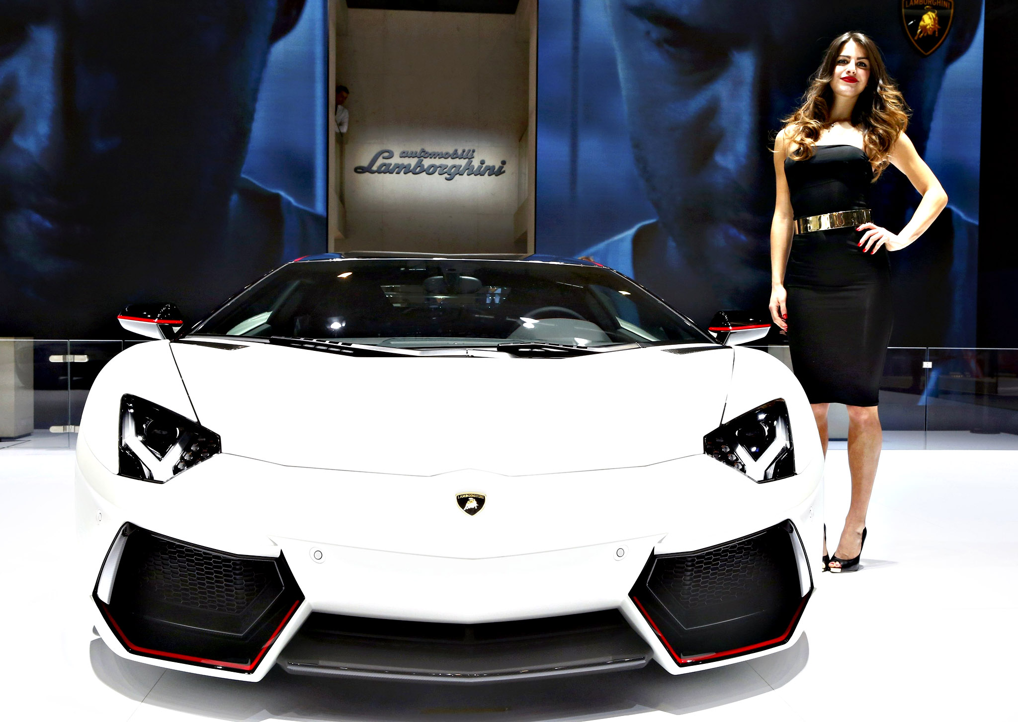 A model poses next to a Lamborghini Aventador LP 700-4 during the second press day ahead of the 85th International Motor Show in Geneva March 4, 2015.