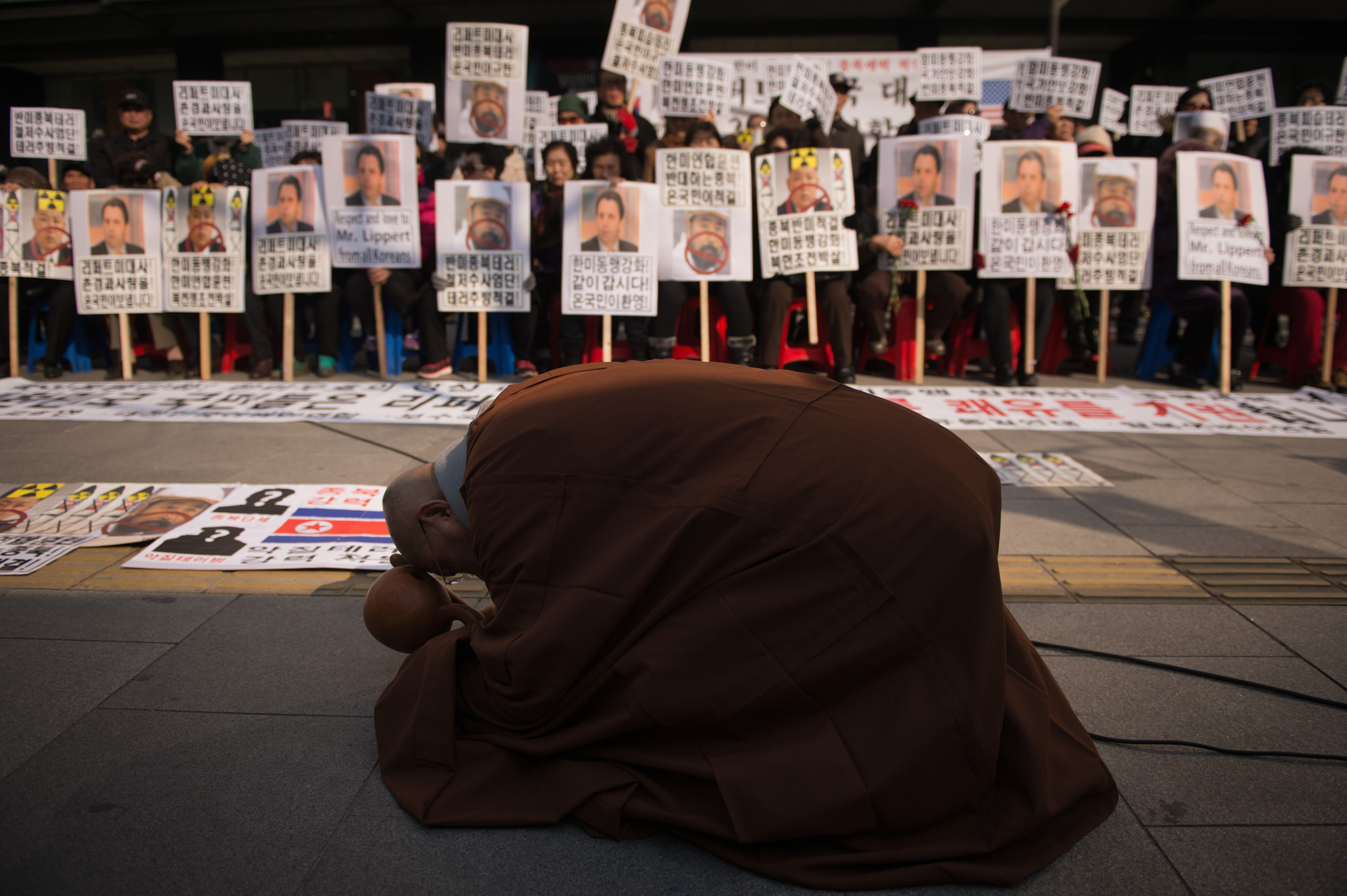 A monk prays before anti-North Korea activists holding placards in support of US Ambassador to Seoul Mark Lippert, during a rally in Seoul on March 6, 2015. South Korea has reacted with shock and a little shame to a violent knife attack on Lippert that jarred harshly with the image of a largely safe, well-ordered society.