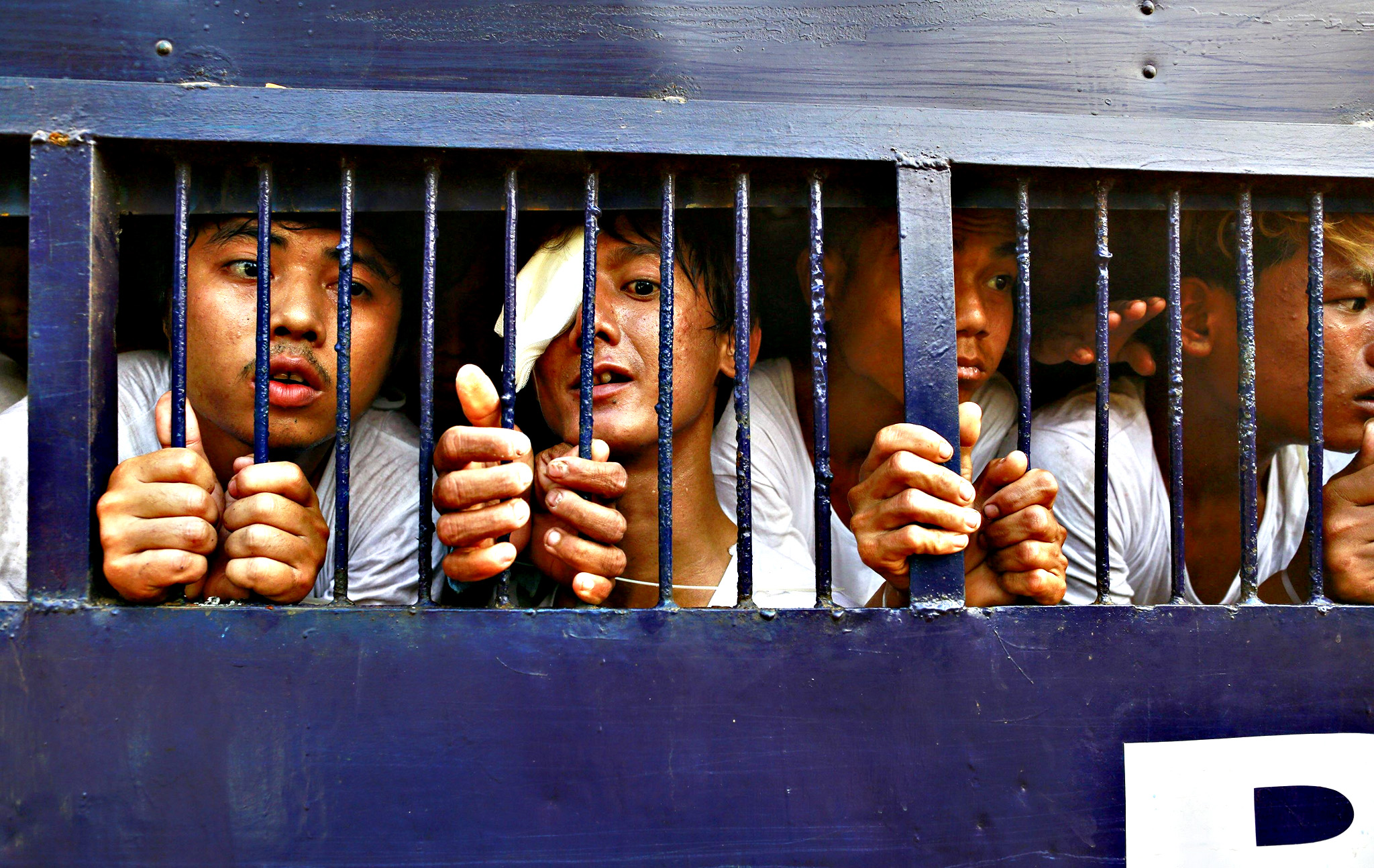 Student protesters try to speak to their family members from a prison vehicle as they are transported to a court in Letpadan on Wednesday. Myanmar's opposition National League for Democracy (NLD) demanded an inquiry on Wednesday into clashes between police and protesters in which students, monks and journalists were beaten with batons and more than 100 people were arrested