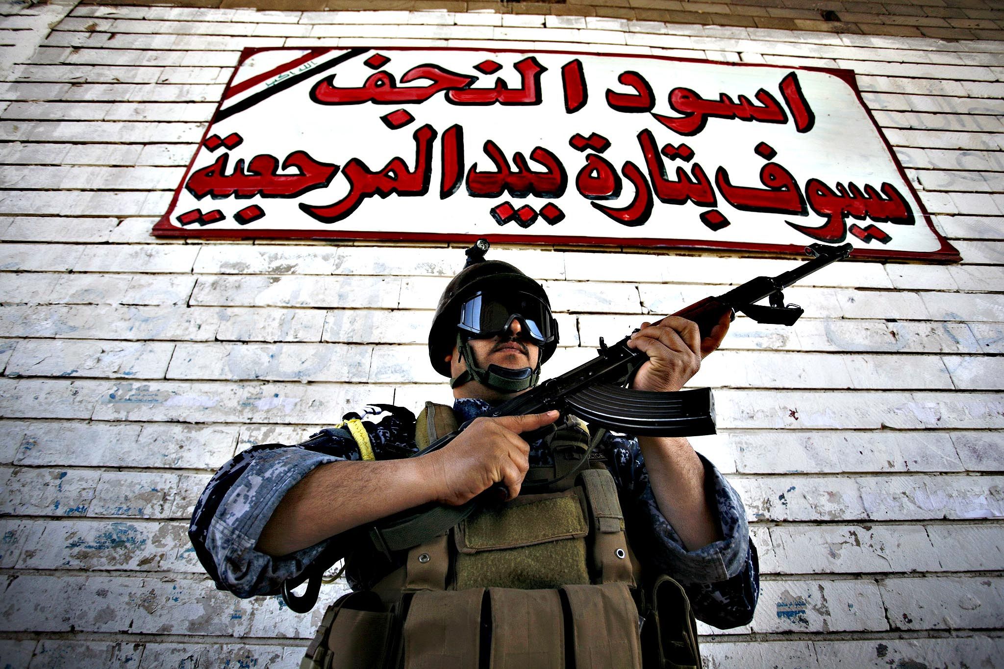 "An Iraqi Shiite fighter from the Popular Mobilisation units, part of the Zahraa Brigade, poses for a picture under a sign which reads in Arabic ""Lions of Najaf"" during a training exercise in the central Iraqi city of Kufa, some 160 kms south of Baghdad, on March 23, 2015."