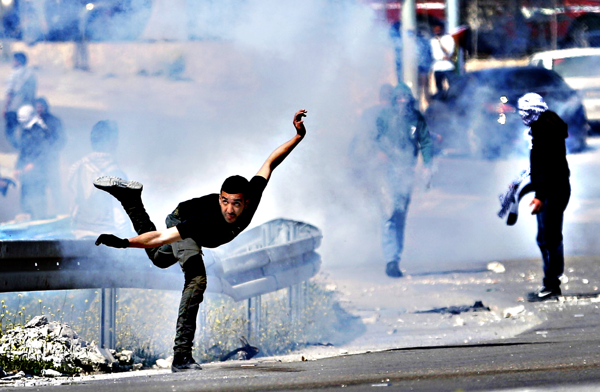 A Palestinian protester returns a tear gas canister fired by Israeli troops during a protest against what Palestinians say is land confiscation by Israel for Jewish settlements, near the West Bank town of Abu Dis near Jerusalem March 17, 2015.