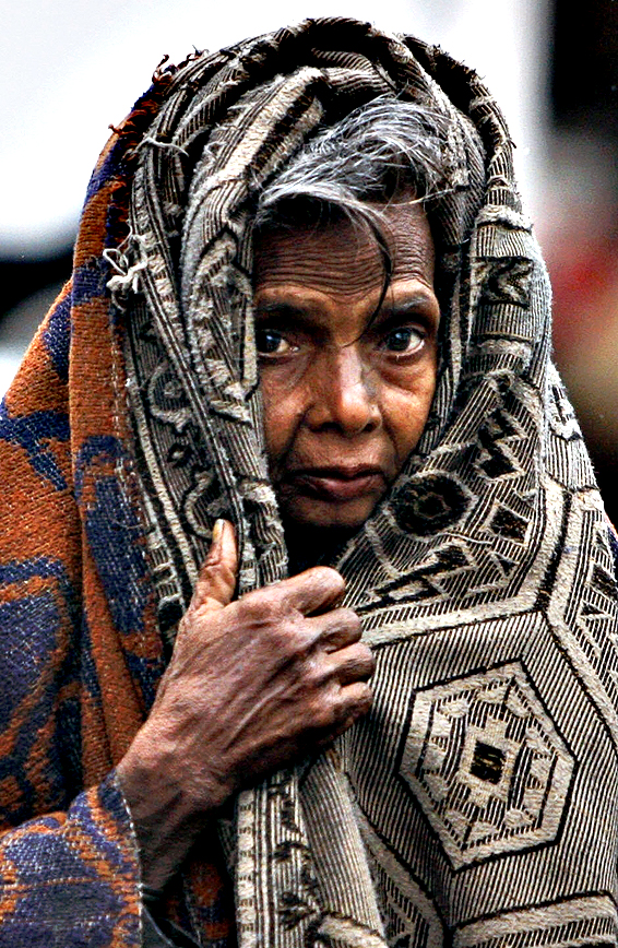 An Indian homeless woman covers herself with a woolen cloth as it rains in Jammu, India, Monday, March 2, 2015. The Jammu-Srinagar highway was closed for all vehicular traffic because of heavy snowfall in the Kashmir valley.