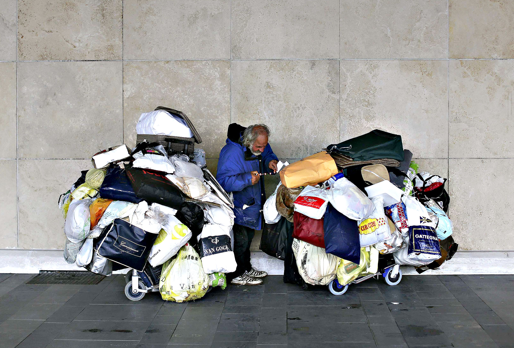 A man stands between two trolleys loaded with bags containing his clothes and personal belongings outside the entrance of Fiumicino international airport in Rome...A man stands between two trolleys loaded with bags containing his clothes and personal belongings outside the entrance of Fiumicino international airport in Rome March 16, 2015.