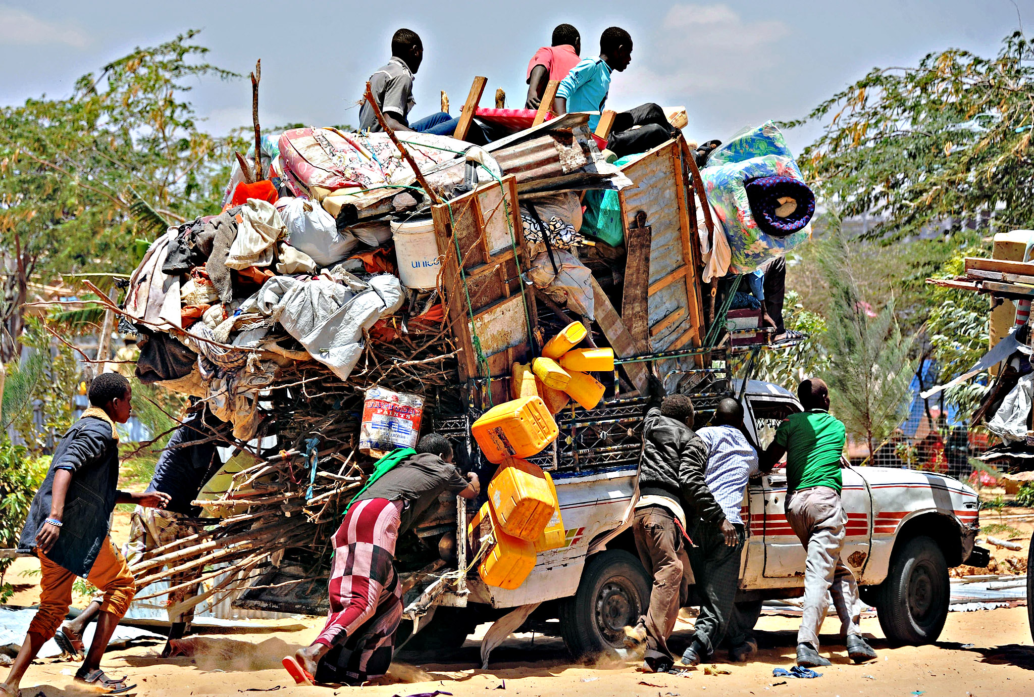 Somali refugees carry their belongings after their temporary shelters were destroyed by Somali soldiers on March 4, 2015 at the Sarkusta refugee camp in southern Mogadishu. Dozens of houses and shops were destroyed in the area after the Somali government ordered the demolition of makeshift homes.