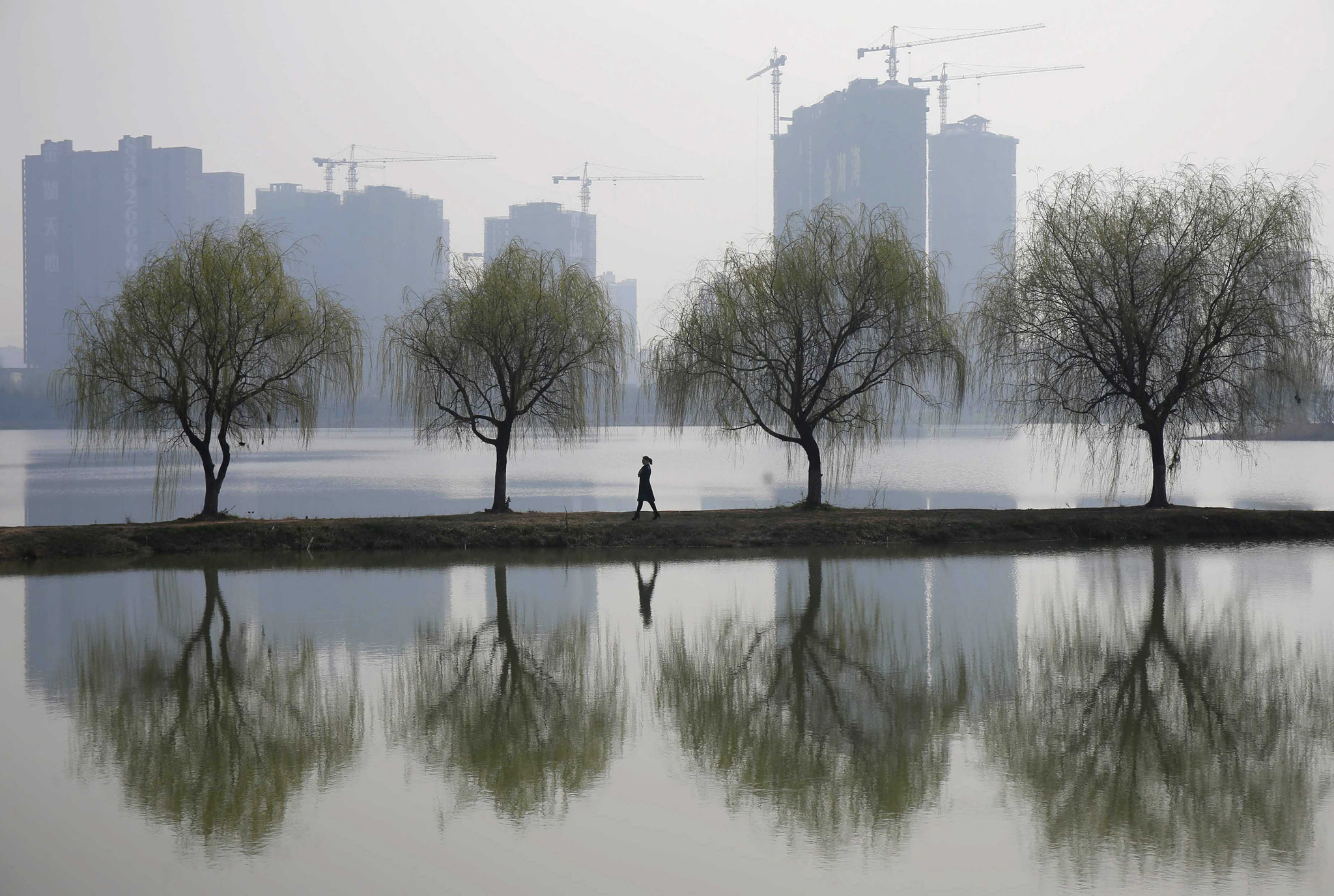 A woman walks past trees reflected on a lake in front of a construction site of a residential compound on a hazy day in Wuhan, Hubei province