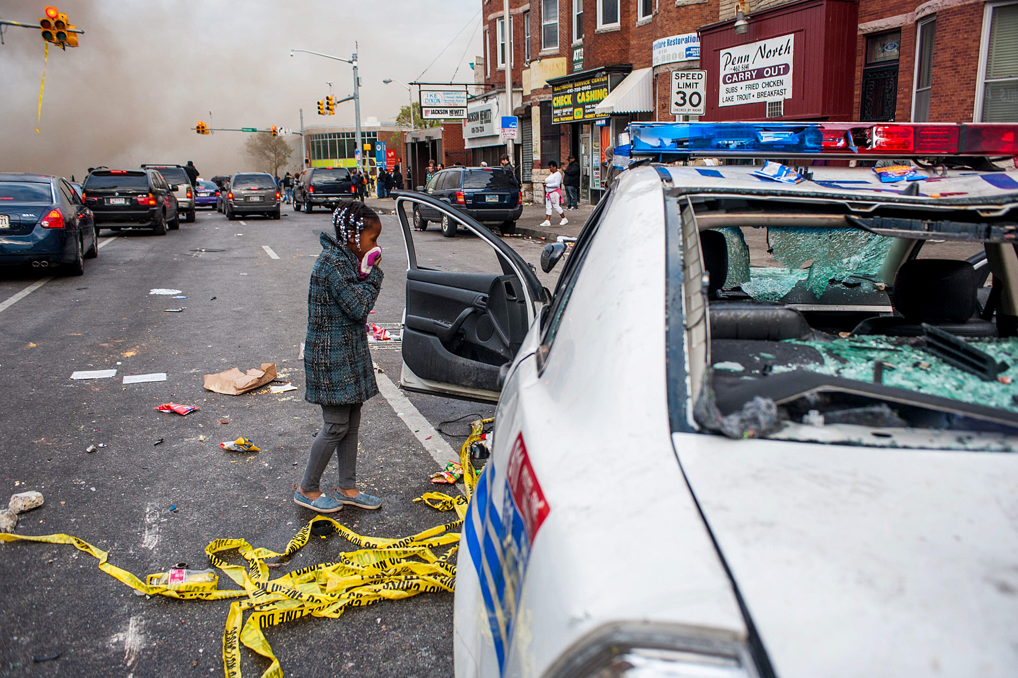 Demonstrators Gather Outside Baltimore Police Station to Protest Death of Freddie Gray...epa04723487 A young girl peers into a destroyed Baltimore City Police car along North Avenue near a CVS that was on fire during a protest for the death of Freddie Gray in Baltimore, Maryland, USA, 27 April 2015. Gray died of spinal cord injuries on 19 April while in police custody; the US Justice Department announced that they are launching their own investigation into the case.  EPA/NOAH SCIALOM