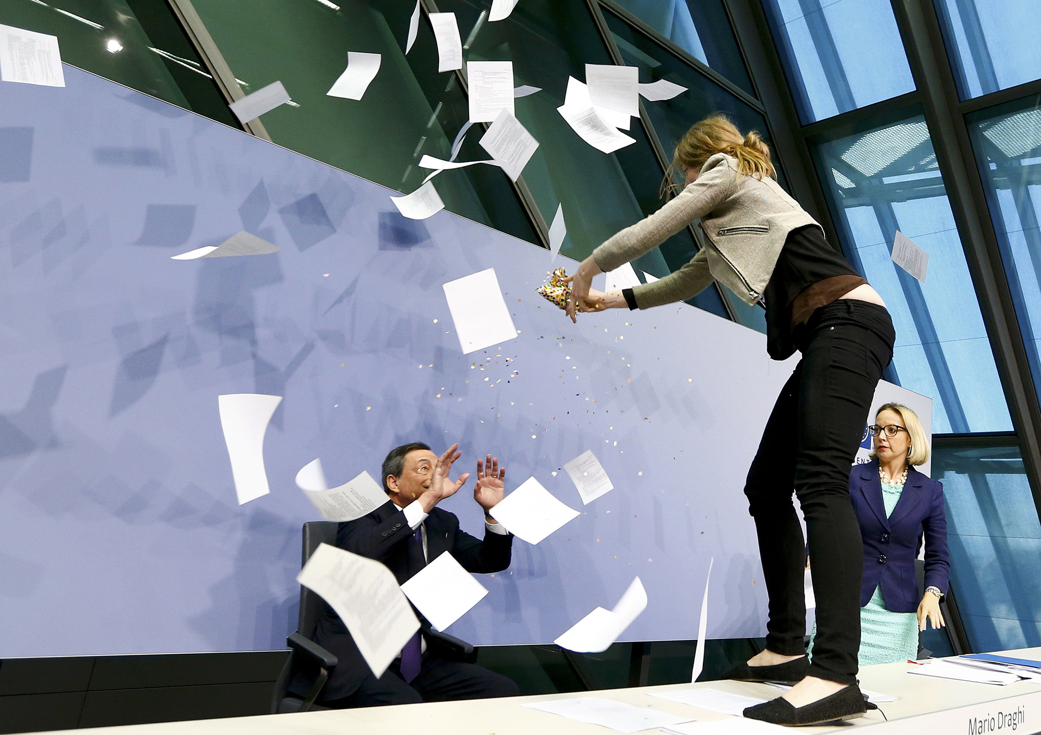A protester jumps on the table in front of the European Central Bank President Draghi during a news conference in Frankfurt...A protester jumps on the table in front of the European Central Bank President Mario Draghi during a news conference in Frankfurt, April 15, 2015. The news conference was disrupted on Wednesday when a woman in a black T-shirt jumped on the podium.   REUTERS/Ralph Orlowski  TPX IMAGES OF THE DAY