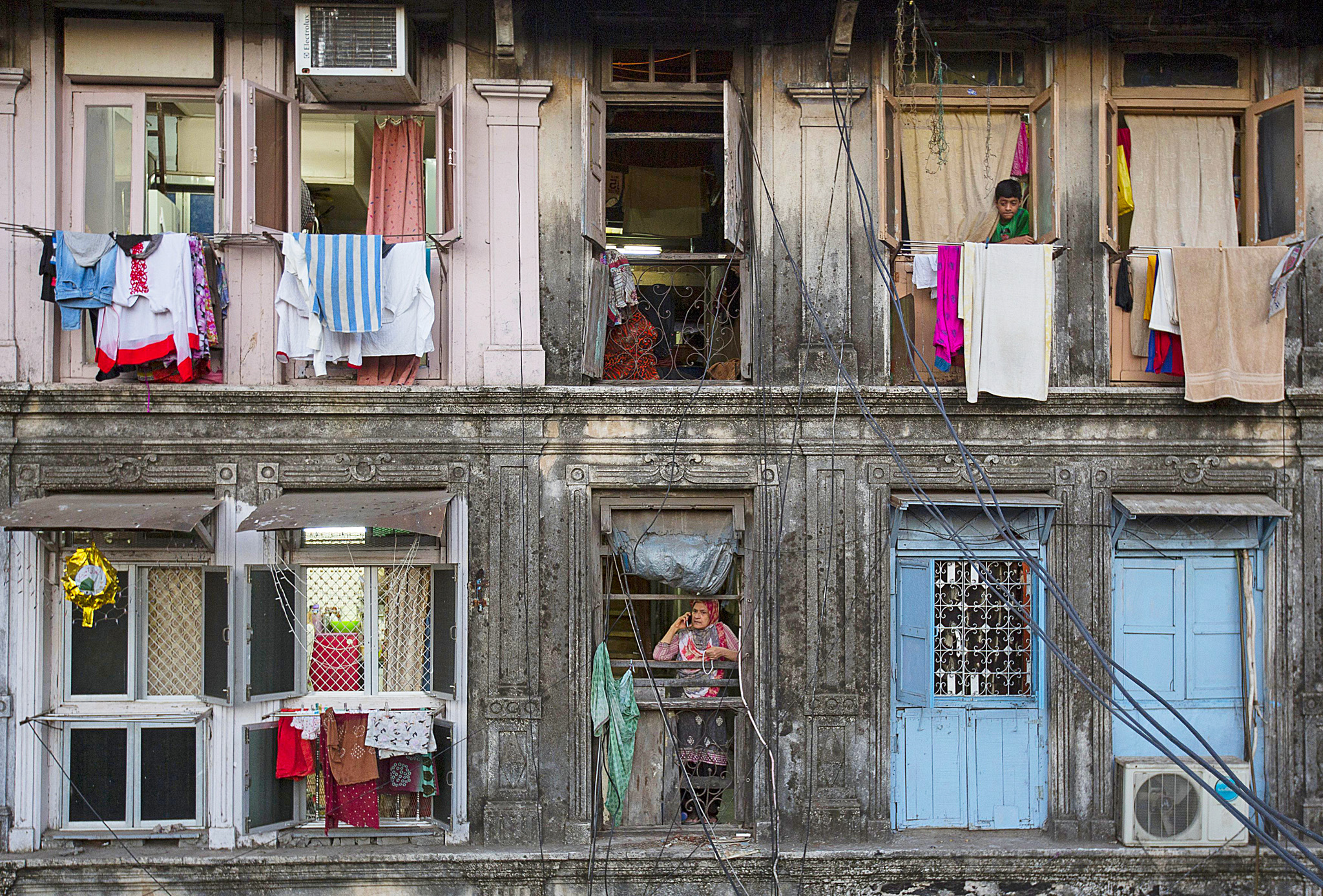 "Wider Image: Renting in Mumbai Per Square Foot...Residents look out of windows of an apartment in Mumbai March 15, 2015. The cost for buying a 200 square feet (18 square meters) one-bedroom apartment in this building is around 25,000 Indian rupees per square feet ($ 400) or 5,000,000 Indian rupees ($ 80,000). The rent for an apartment in the same building is around 12,000 Indian rupees ($ 190) per month. REUTERS/Danish Siddiqui  TPX IMAGES OF THE DAY PICTURE 05 OF 22 FOR WIDER IMAGE STORY ""RENTING IN MUMBAI PER SQUARE FOOT"" SEARCH ""RENTING SIDDIQUI"" FOR ALL IMAGES"