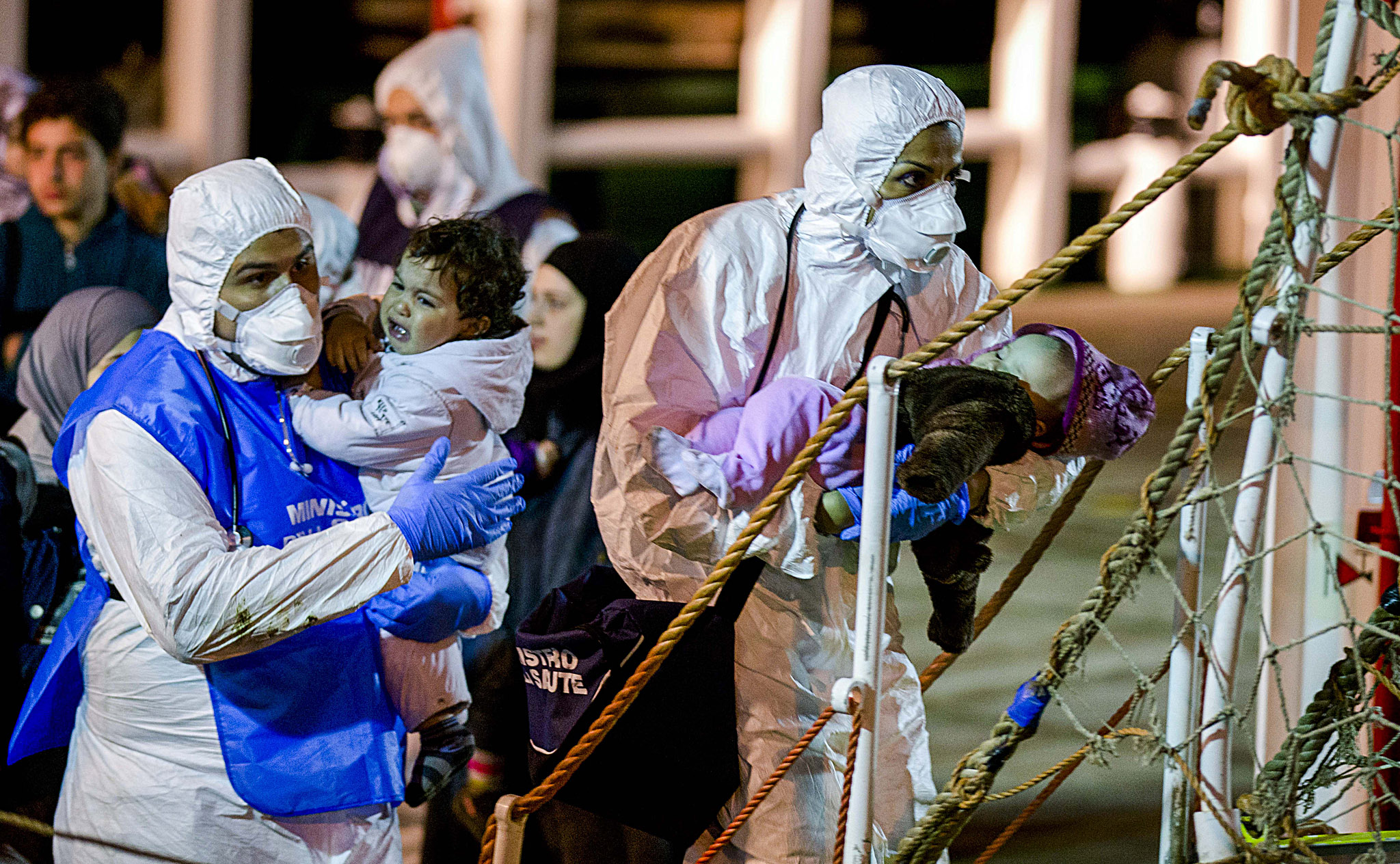 Rescuers help children to disembark in the Sicilian harbor of Pozzallo, Italy, early Monday, April 20, 2015. About 100 migrants, including 28 children, were rescued on Sunday by a merchant vessel in the Sicilian Strait while they were trying to cross. Another smuggler's boat crammed with hundreds of people overturned off Libya's coast on Saturday as rescuers approached, causing what could be the Mediterranean's deadliest known migrant tragedy and intensifying pressure on the European Union Sunday to finally meet demands for decisive action. (AP Photo/Alessandra Tarantino)