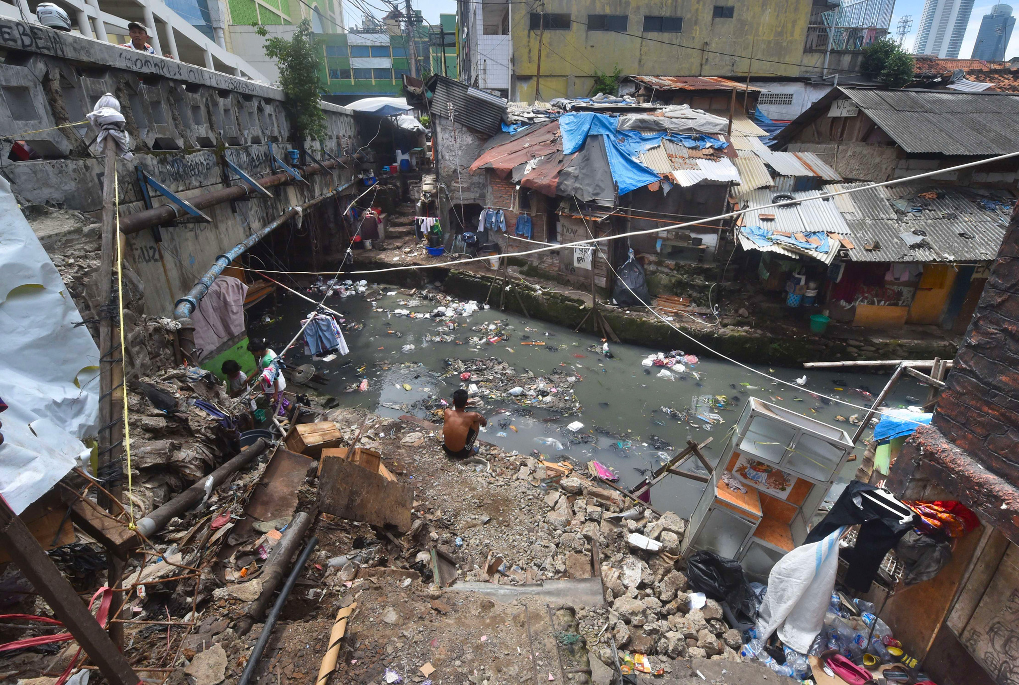 A man squats by the river banks...TOPSHOTS A man squats by the river banks next to shanty houses in downtown Jakarta on April 7, 2015