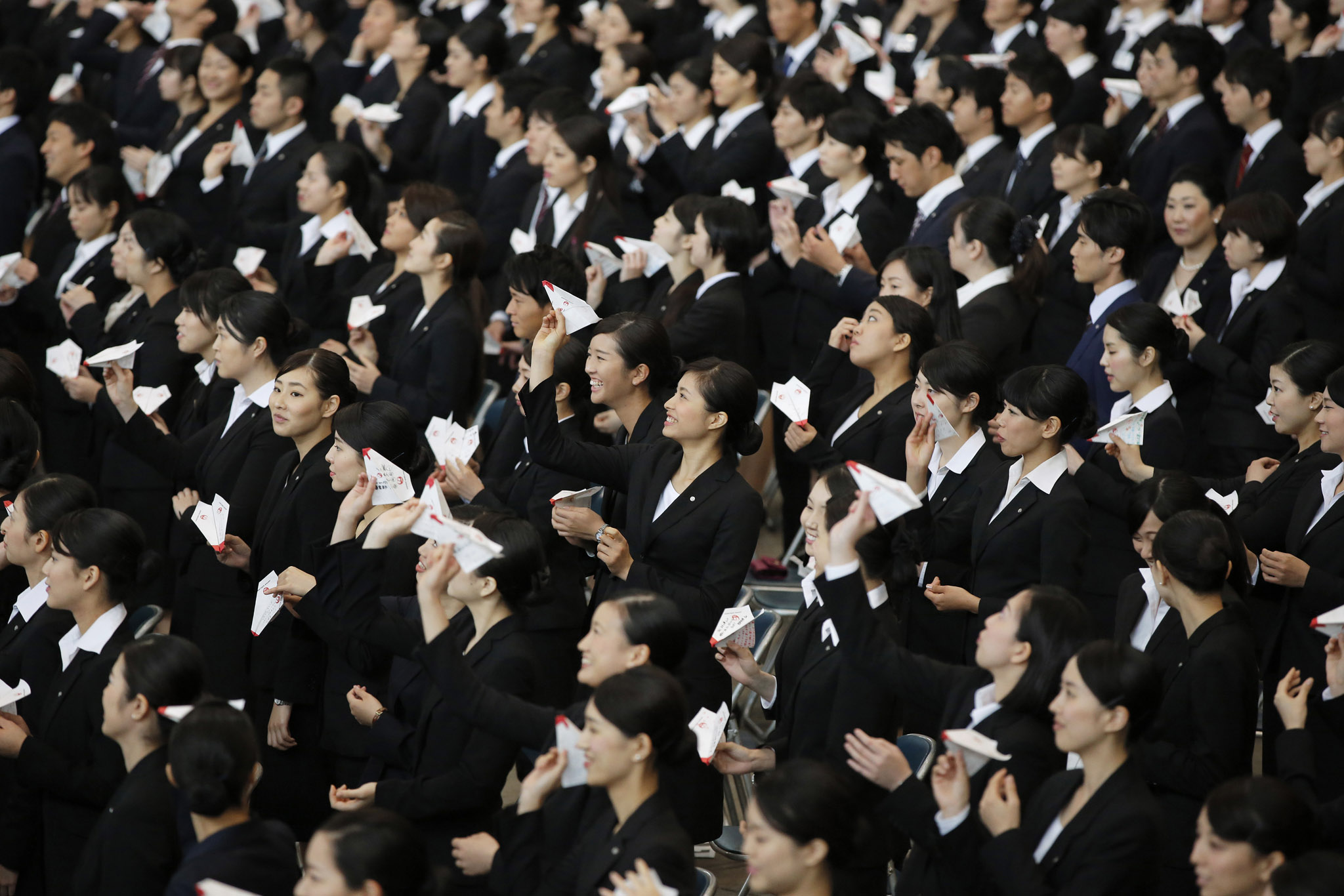 Japan Airlines Co. (JAL) group companies' new employees practice before releasing paper planes during an initiation ceremony at the company's hangar near Haneda Airport in Tokyo, Japan