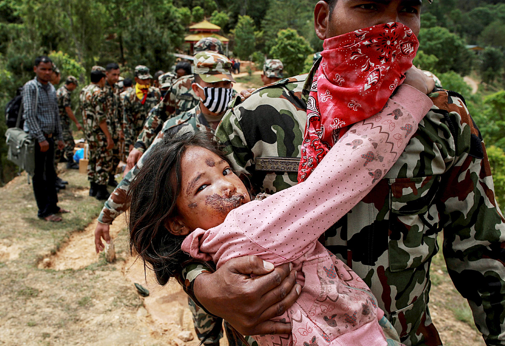 An injured girl is carried by a Nepal Army personnel to a helicopter following Saturday's earthquake in Sindhupalchowk, Nepal,