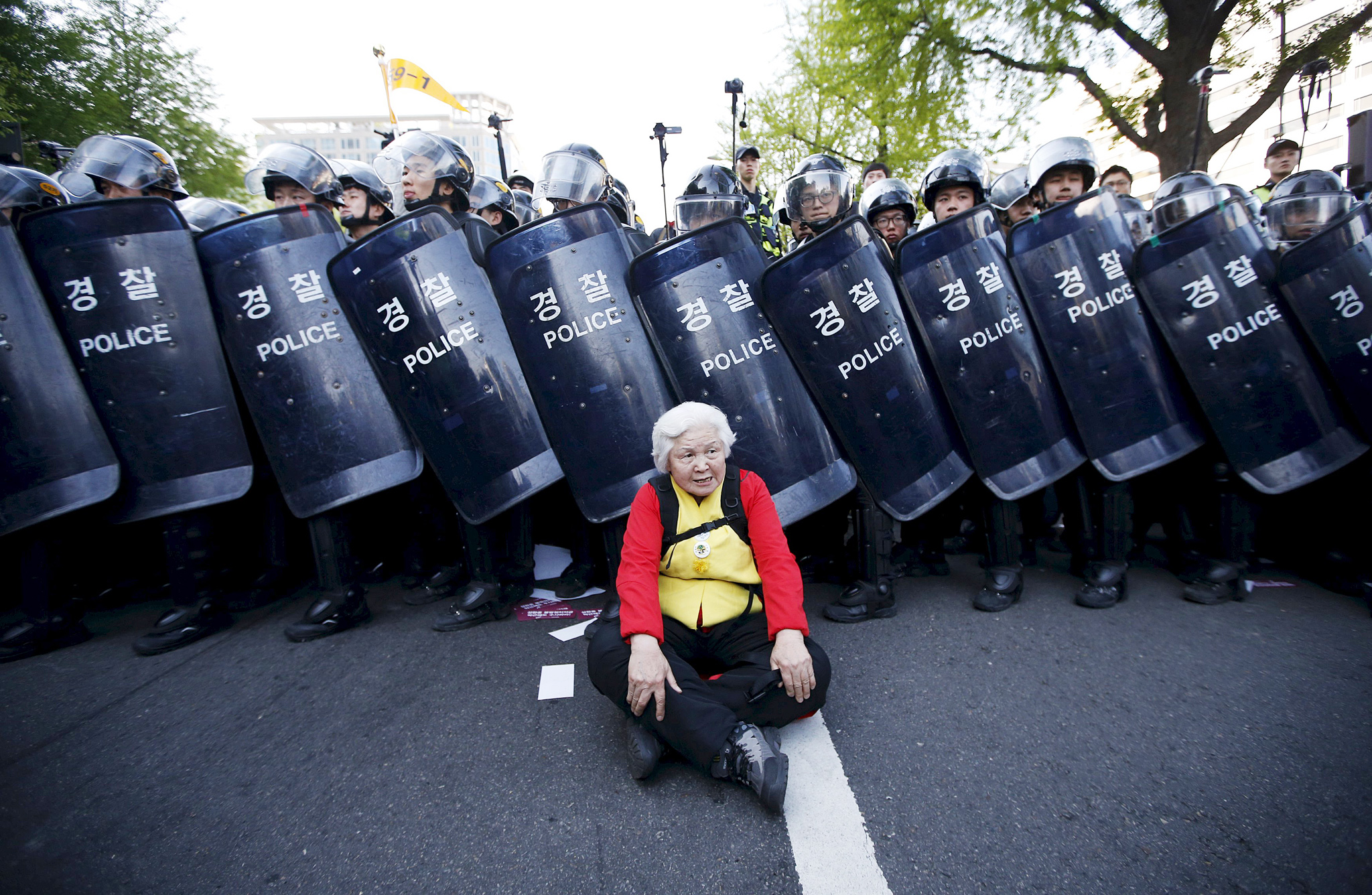 An elderly woman sits on ground as she is blocked by barricade of policemen while marching down street during rally in central Seoul...An elderly woman sits on the ground as she is blocked by a barricade of policemen while marching down the street during a rally in central Seoul, South Korea, April 24, 2015. About 260,000 workers took part in the nationwide one-day strike, including about 60,000 government employees and 10,000 teachers, according to the Korean Federation of Trade Unions. They protested against the government's push to cut pensions and ease rules for firing employees, according to local media.  REUTERS/Kim Hong-Ji