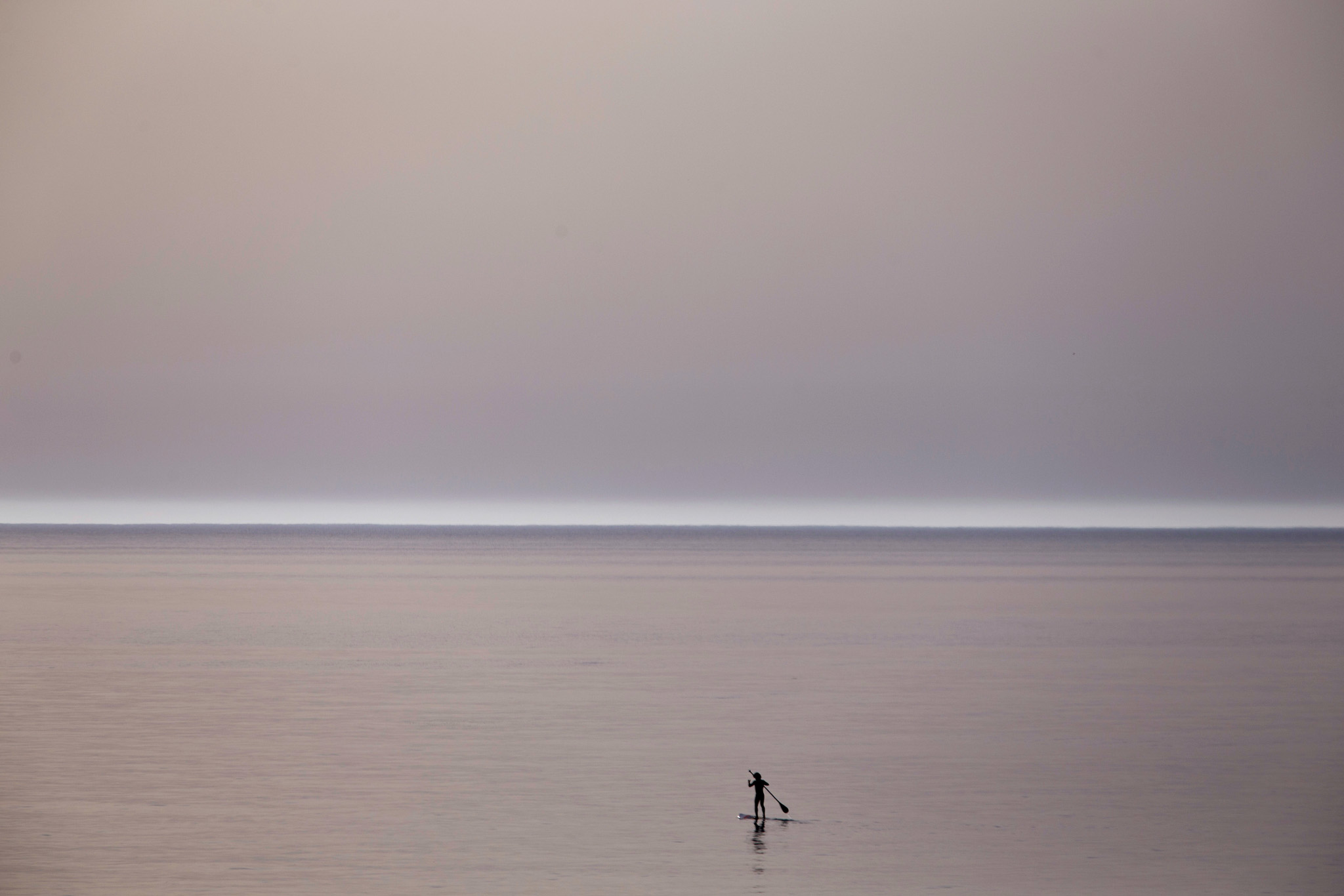 A surfer paddles in a peaceful and quiet Mediterranean sea near Beit Yanai, Israel, Tuesday, April 7, 2015, during the Passover holiday on a warm spring day. (AP Photo/Ariel Schalit)