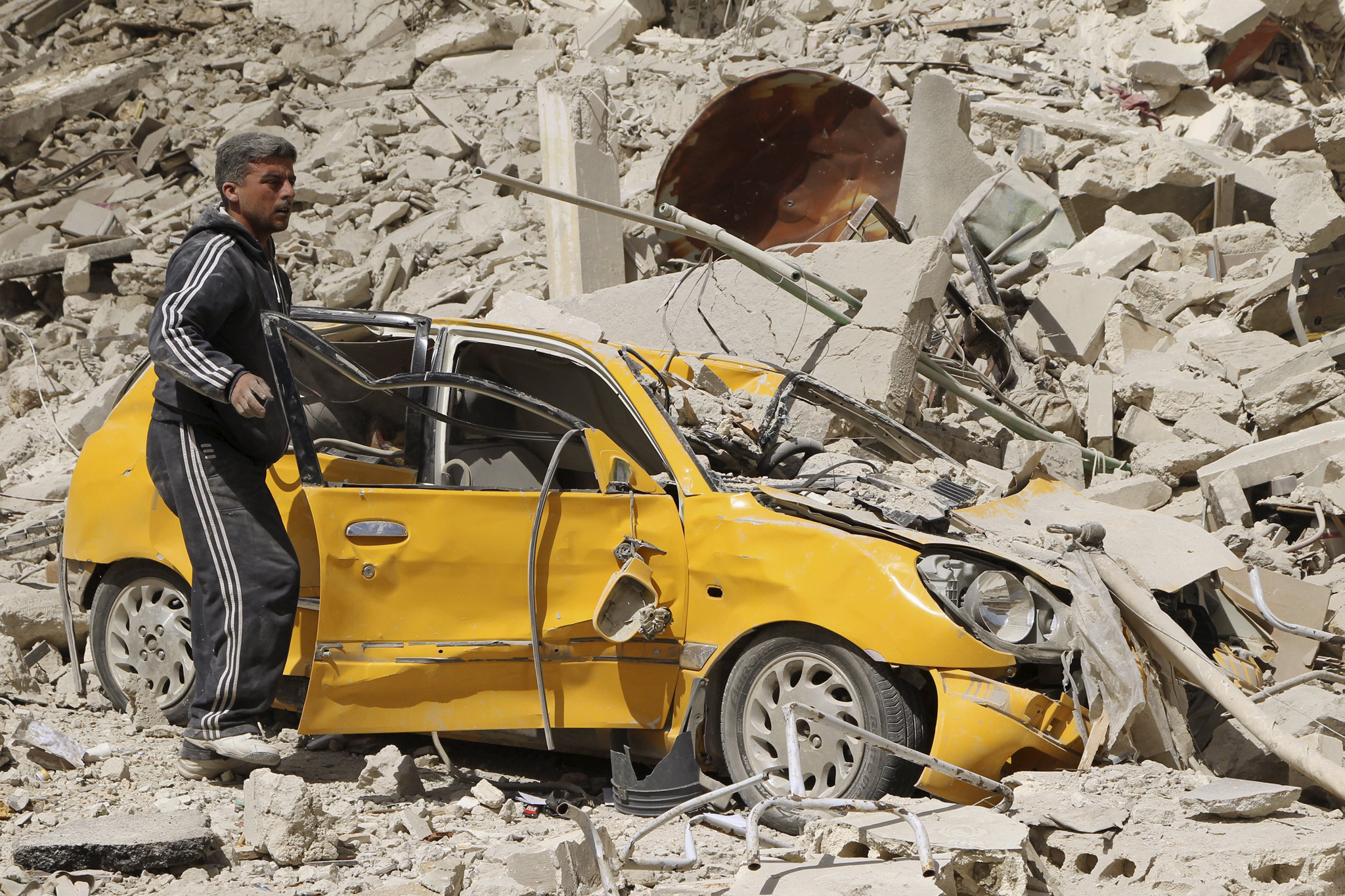 A man searches for belongings in a damaged car at a site hit by what activists said were barrel bombs dropped by forces of Syria's President Bashar al-Assad, at al-Thawra neighborhood in Idlib city today
