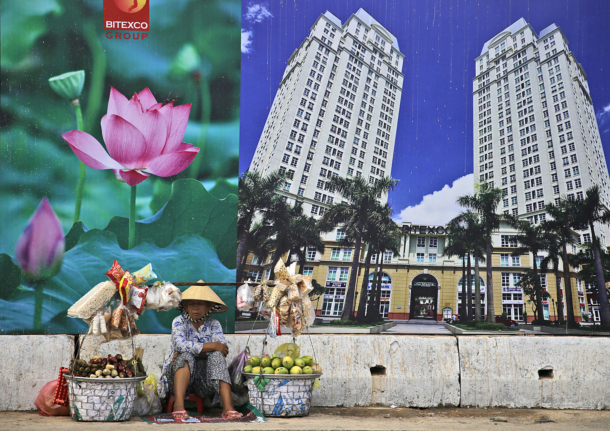 A snack and fruit vendor waits for customers near the advertisement board of a shopping mall and apartment building in Ho Chi Minh City, Vietnam, Wednesday, April 29, 2015. The country is set to celebrate the 40th anniversary of the end of the Vietnam War on April 30.(AP Photo/Dita Alangkara)