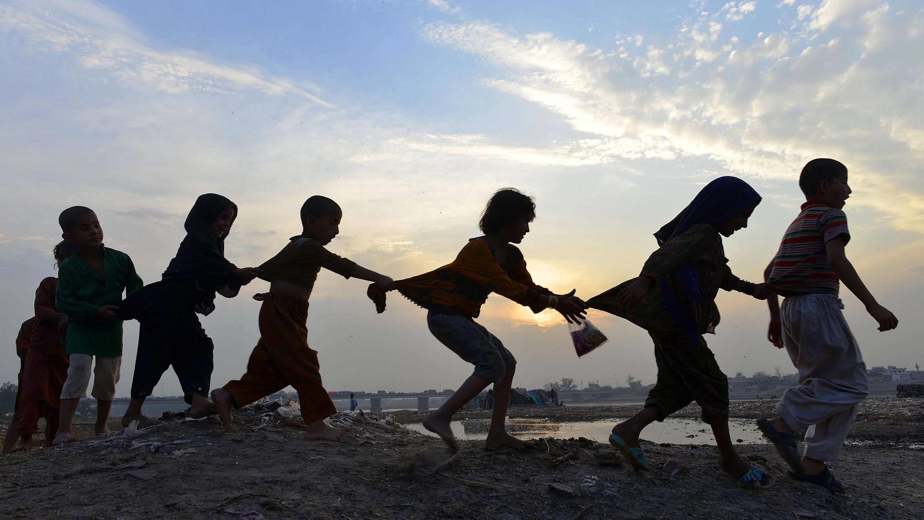 Pakistani children play near the Ravi river in Lahore