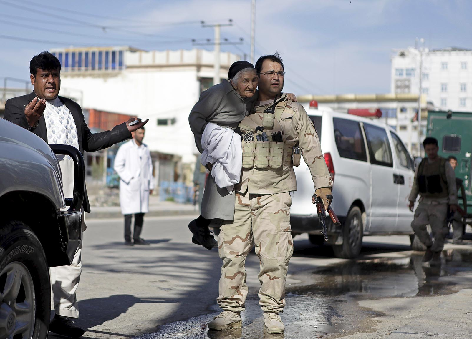 A member of the Afghan security force holds a woman while rescuing her from the site of an attack in Mazar-i-Sharif