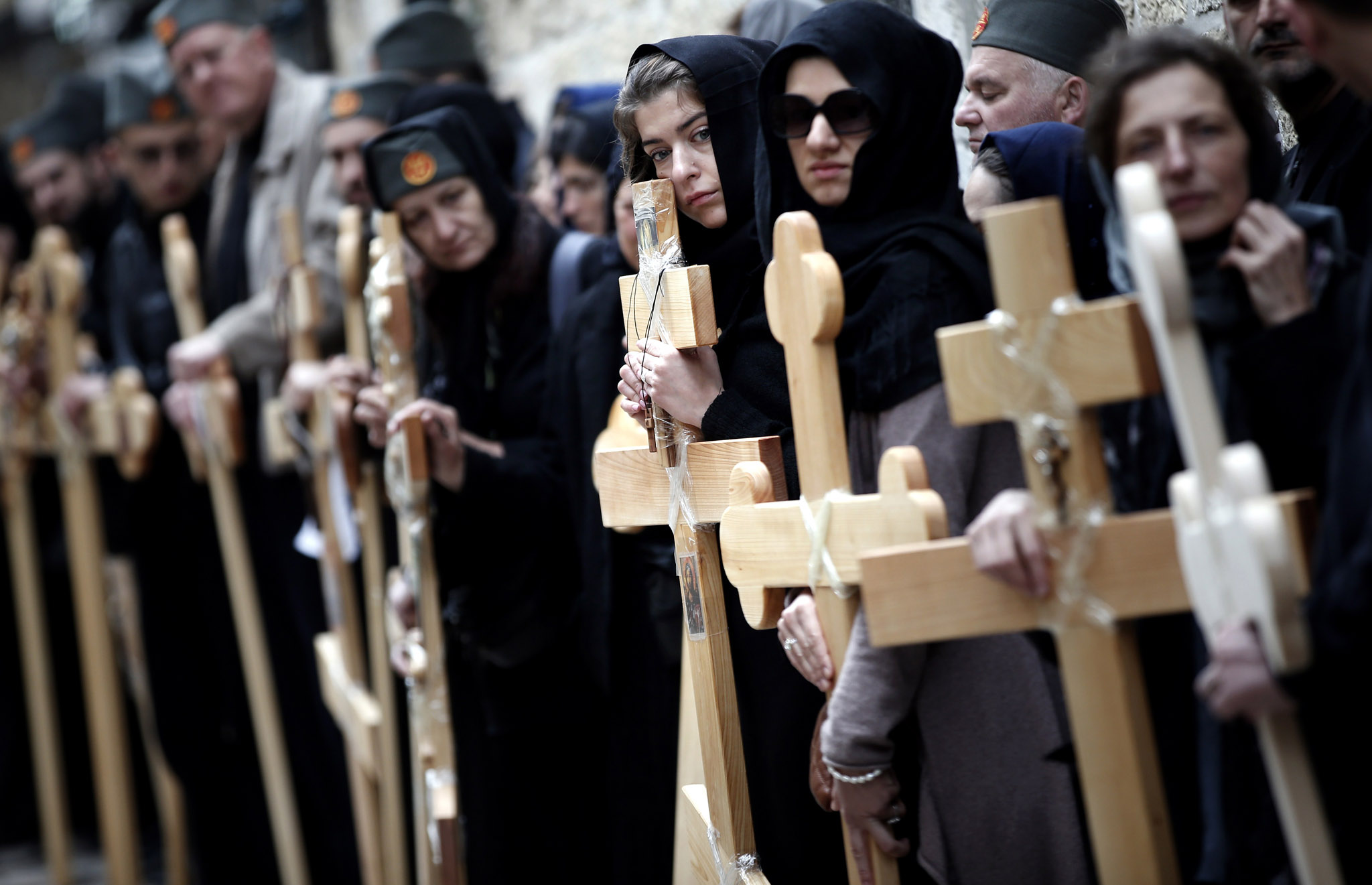 Serbian Orthodox Christian pilgrims pray as they carry wooden crosses, along the Via Dolorosa (Way of Suffering), during the Orthodox Good Friday procession in Jerusalem's old city.