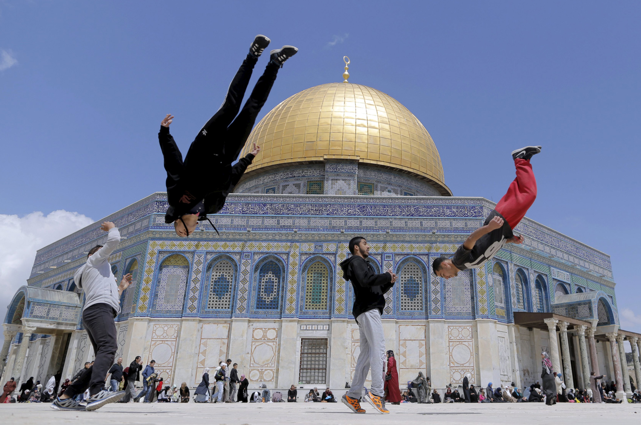 The Dome of the Rock is seen in the background as Palestinian youths practice their parkour skills during Friday prayers in Jerusalem's Old City.