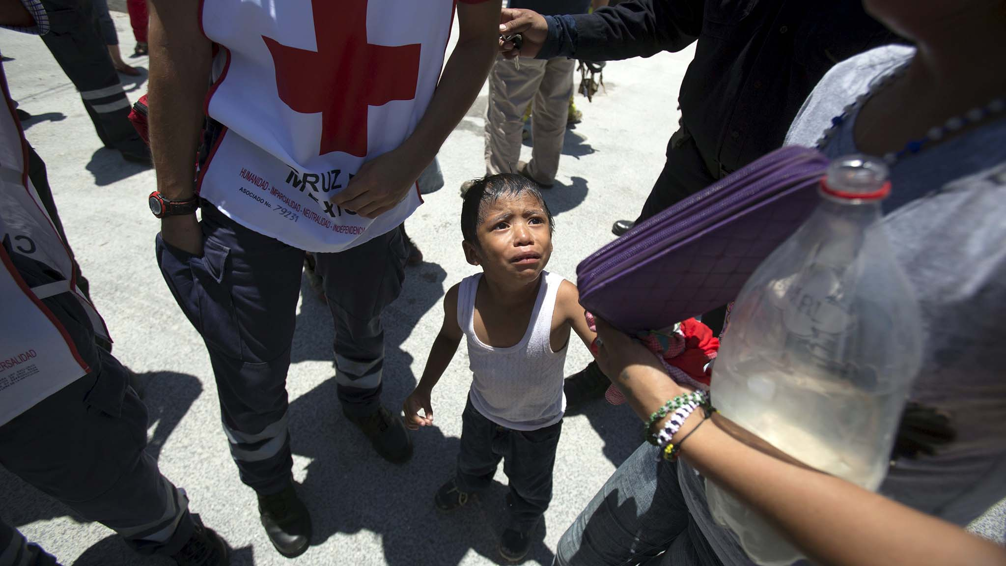 A child experiencing shock is seen next to a Red Cross paramedic outside the jail during a clash of rival groups in the prison of Cancun