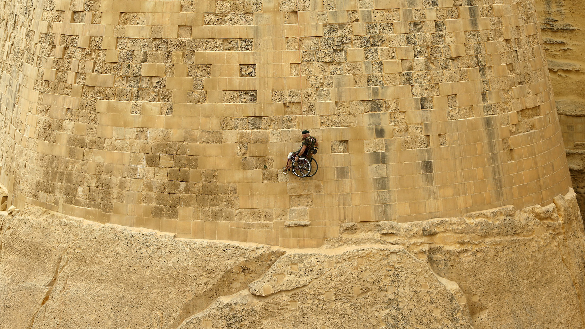 British former police officer Swasie Turner abseils for charity in a wheelchair down the fortification bastions of Valletta, Malta