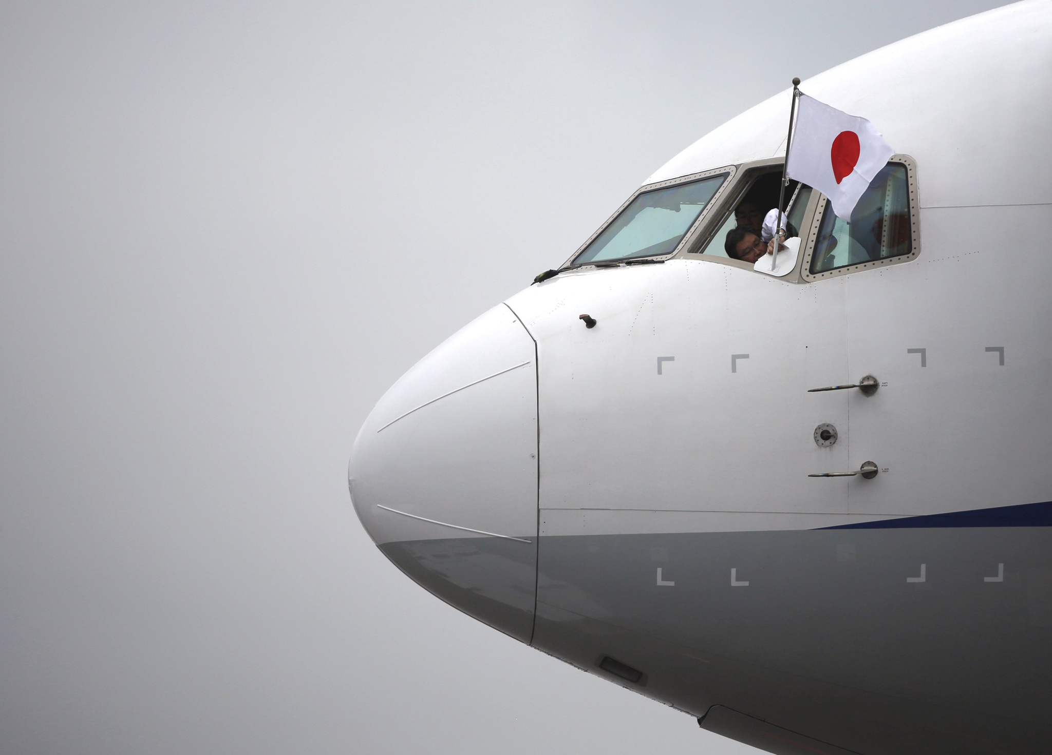 A flight crew member attaches a Japanese national flag on the airplane for Emperor Akihito and Empress Michiko's special flight to Palau before it's take off at Haneda international airport in Tokyo