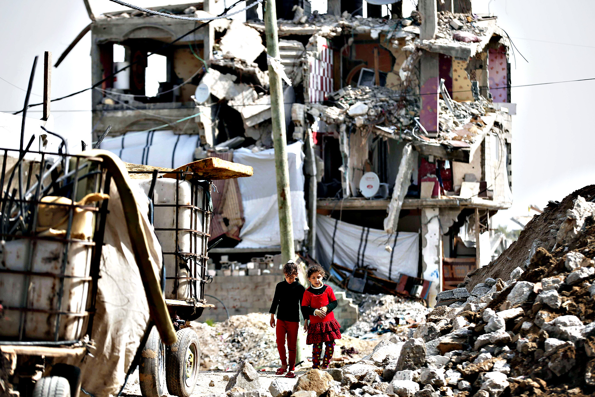 Palestinian girls walk past rubble of heavily damaged buildings on Wednesday in the eastern Gaza City neighborhood of Shejaiya which was destroyed during the 50-day war between Israel and Hamas militants in the summer of 2014.