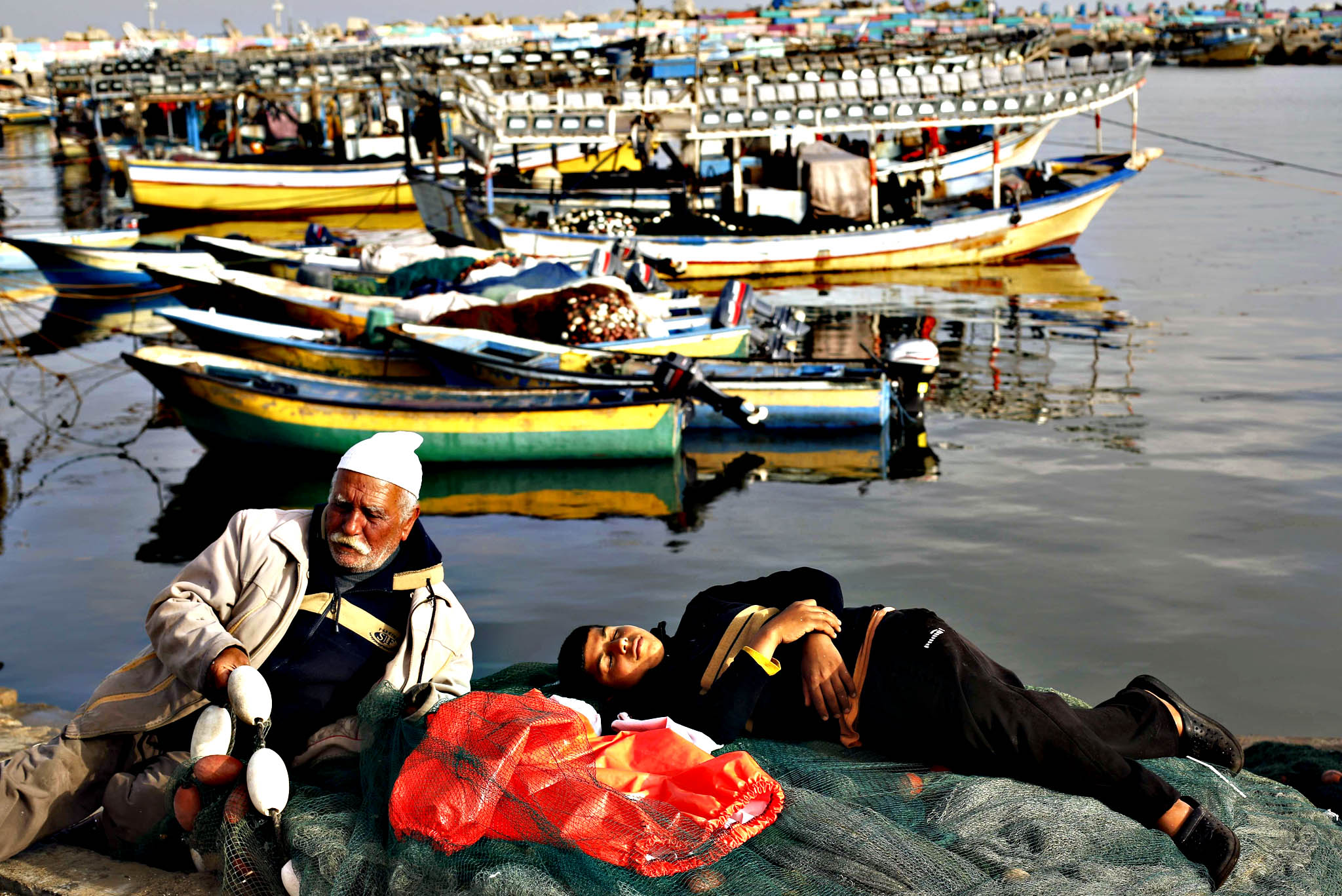 Palestinian fishermen rest after arriving back from a fishing trip at the port of Gaza City on April 21, 2015.