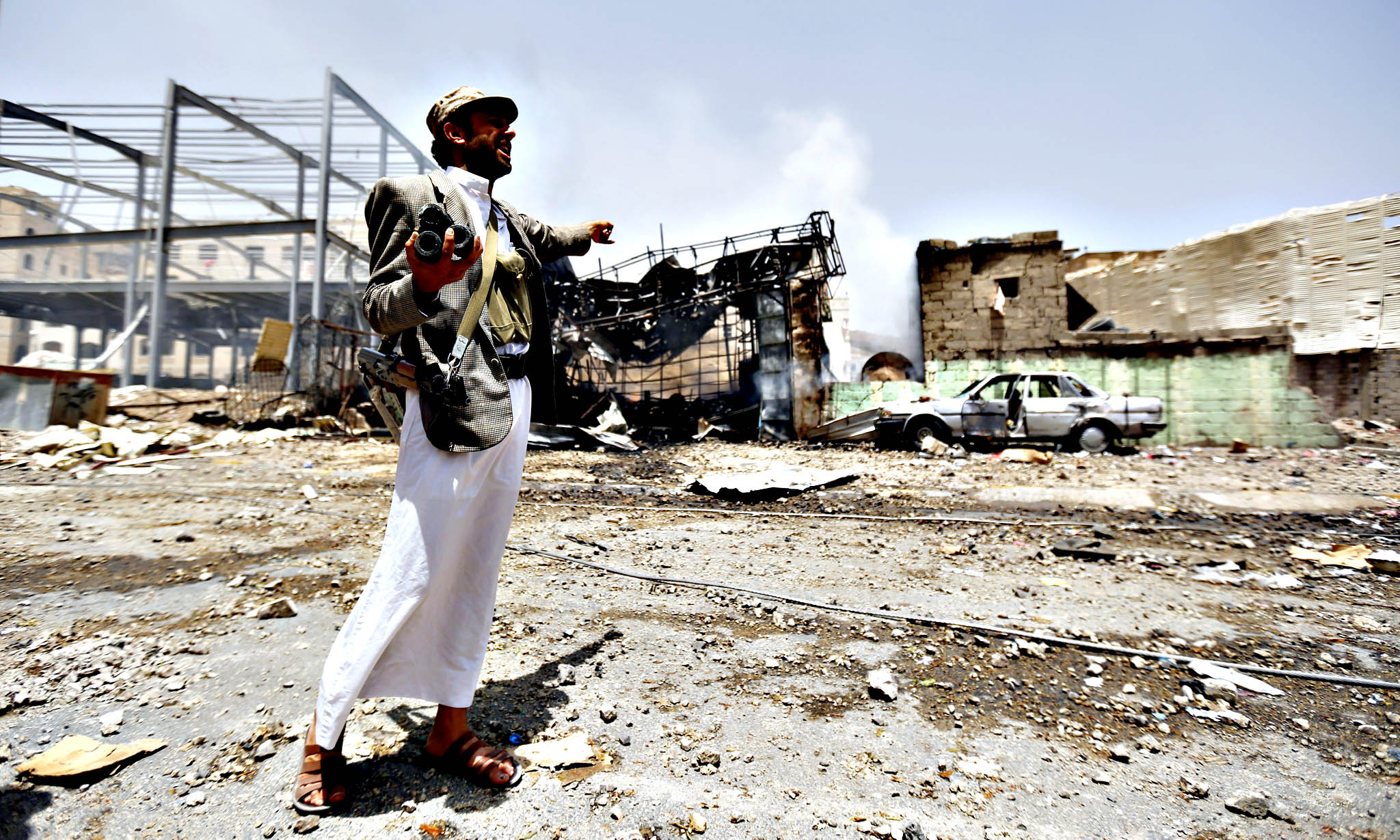 An armed member of the Houthi militia calls for help near a house allegedly destroyed in an airstrike carried out by the Saudi-led coalition targeting two military bases controlled by Houthi fighters in Sana a, Yemen, 20 April 2015. A huge explosion rocked Sana'a as airstrikes carried out by the Saudi-led coalition hit what witnesses said was a base used by a missile brigade of the Yemeni army, but is now controlled by the Houthis, the explosions damaging nearby civilian housing
