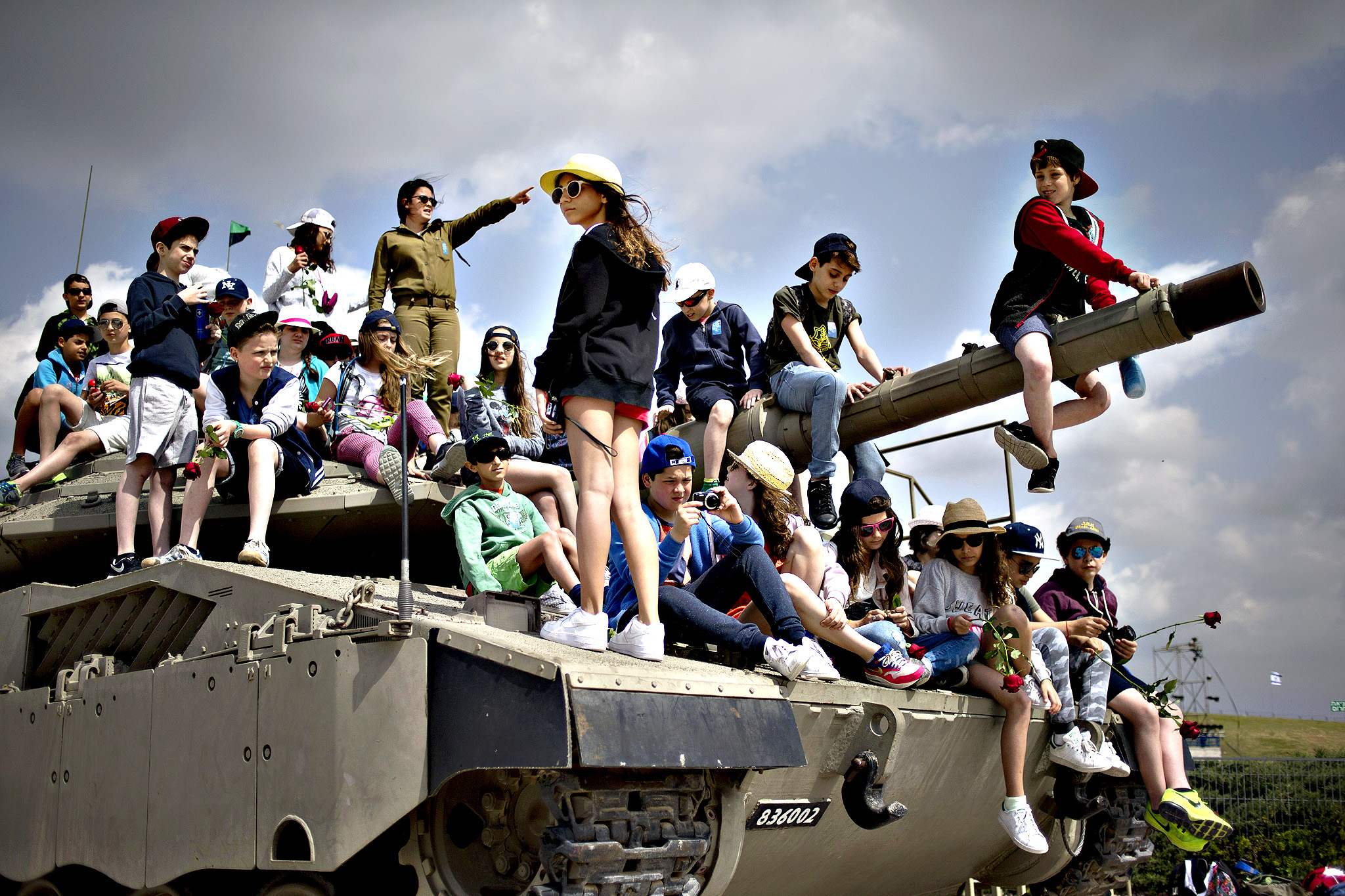 School children from Belgium sit on a tank on display as they listen to an Israeli soldier speaks about Israel's wars, near the wall of names of fallen soldiers, at the Armored Corps memorial, before a ceremony marking the annual Memorial Day for soldiers and civilians killed in more than a century of conflict between Jews and Arabs, in Latrun near Jerusalem, Israel, Wednesday, April 22, 2015. Israel came to a standstill on Wednesday as sirens wailed across the country on its annual Memorial Day for fallen soldiers and victims of terrorism.