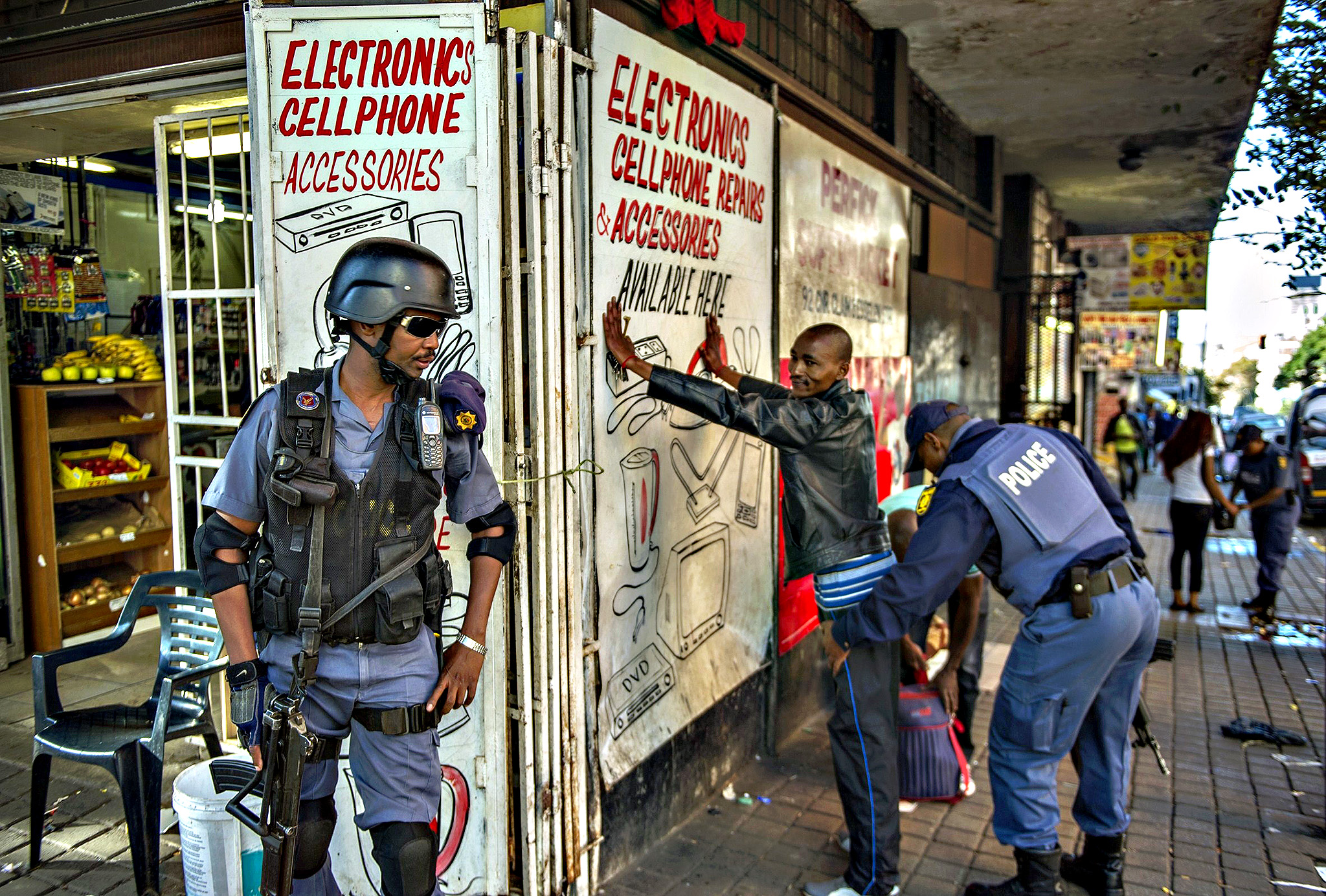 A police officer searches a man as South African Police officers backed by soldiers of the South African Defence Force SADF conduct searches and identity checks in Hilbrow Johannesburg, an area mostly inhabited by foreign nationals, on Monday. At least seven people have been killed in three weeks of unrest that have revived memories of xenophobic bloodshed in 2008, when 62 people were killed mainly in Johannesburg's townships