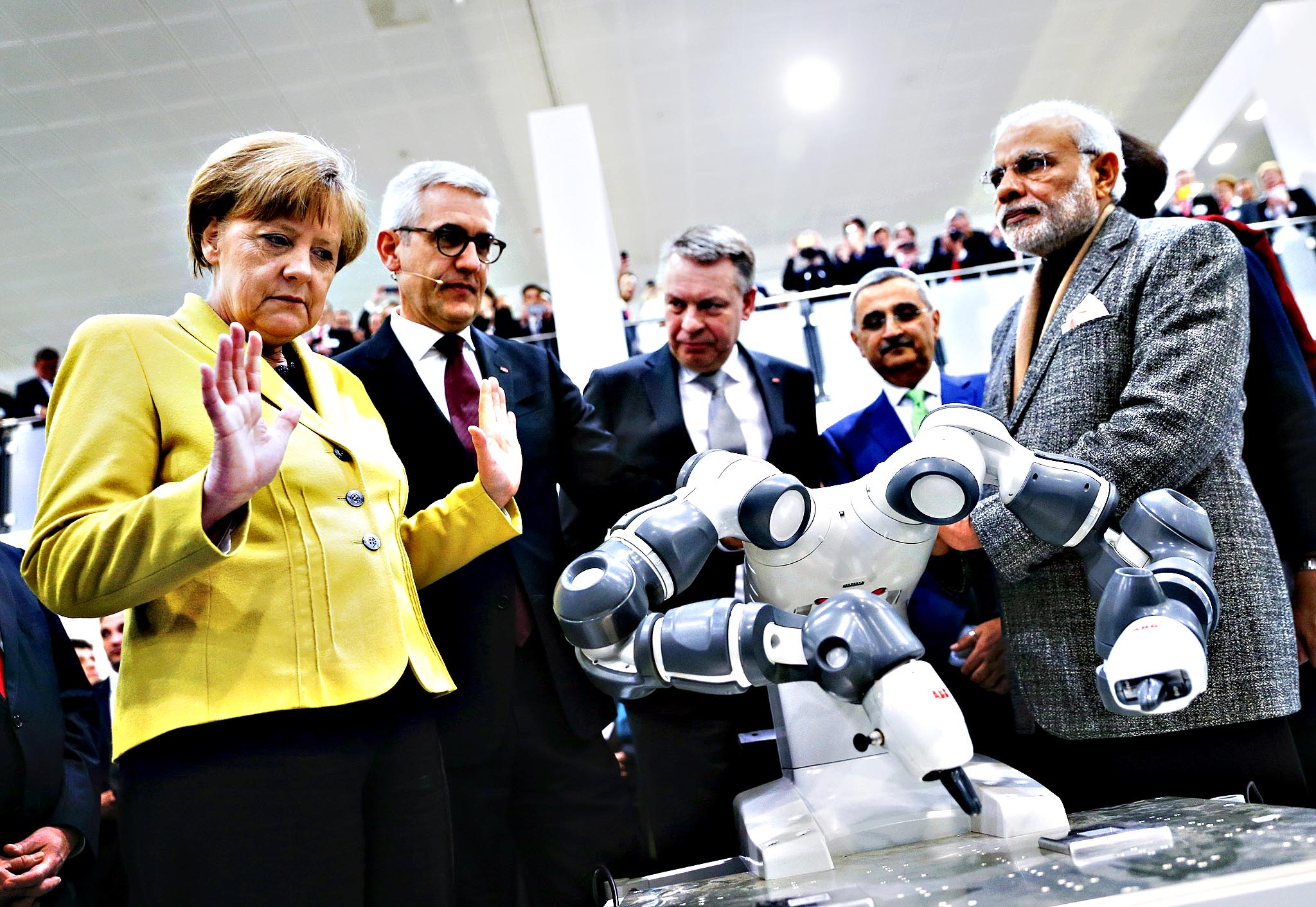 German Chancellor Merkel and Indian Prime Minister Modi look at a UMI robotic arm at the world's largest industrial technology fair, the Hannover Messe, in Hanover...German Chancellor Angela Merkel and Indian Prime Minister Narendra Modi (R) look at a UMI robotic arm at the world's largest industrial technology fair, the Hannover Messe, in Hanover April 13, 2015.
