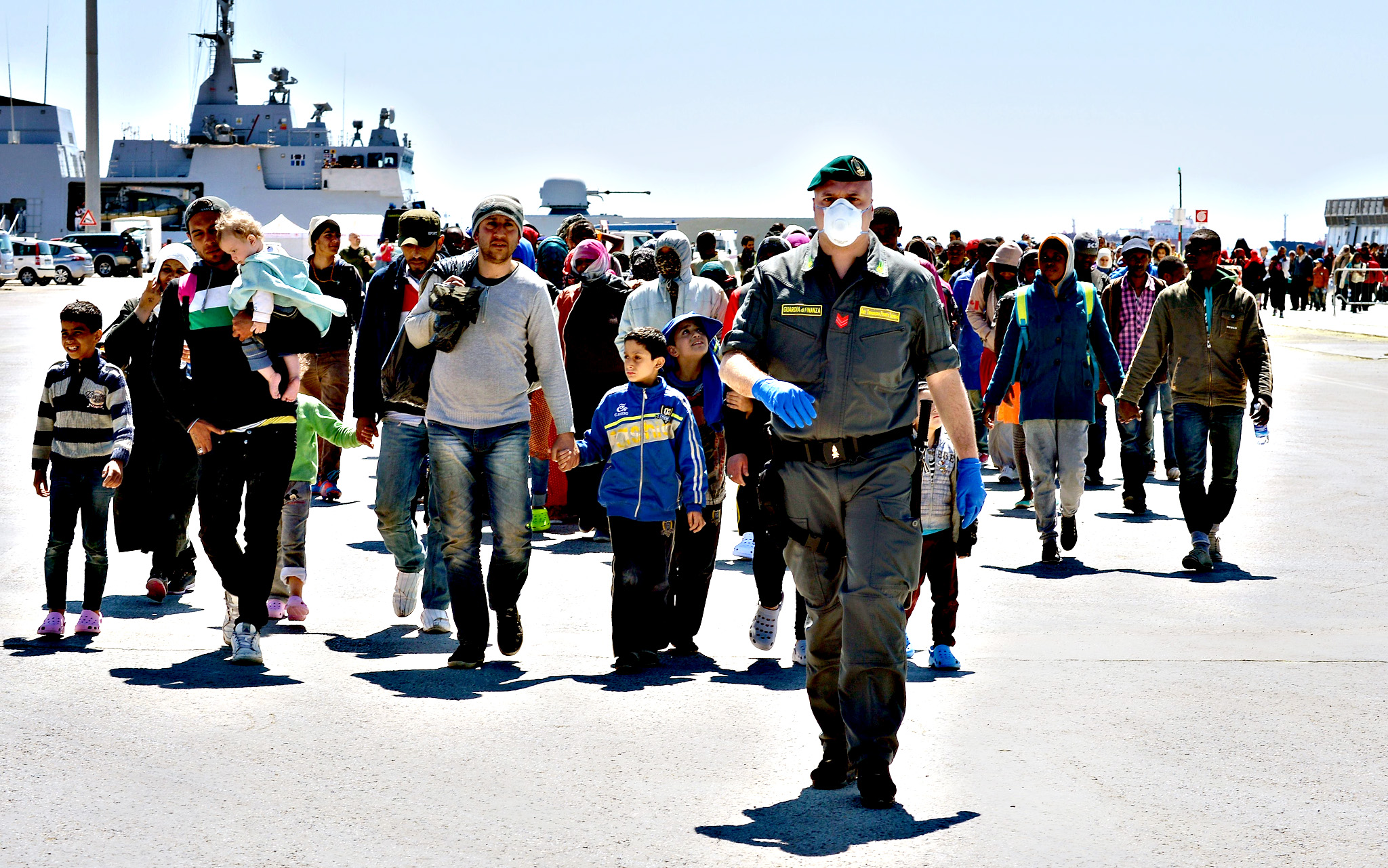 Rescued migrants walk along the quayside after disembarking from the Italian Navy vessel Bettica in the Sicilian harbour of Augusta on Wednesday. European governments came under increasing pressure to tackle the Mediterranean's migrant crisis ahead of an emergency summit, as harrowing details emerged of the fate of hundreds who died in the latest tragedy