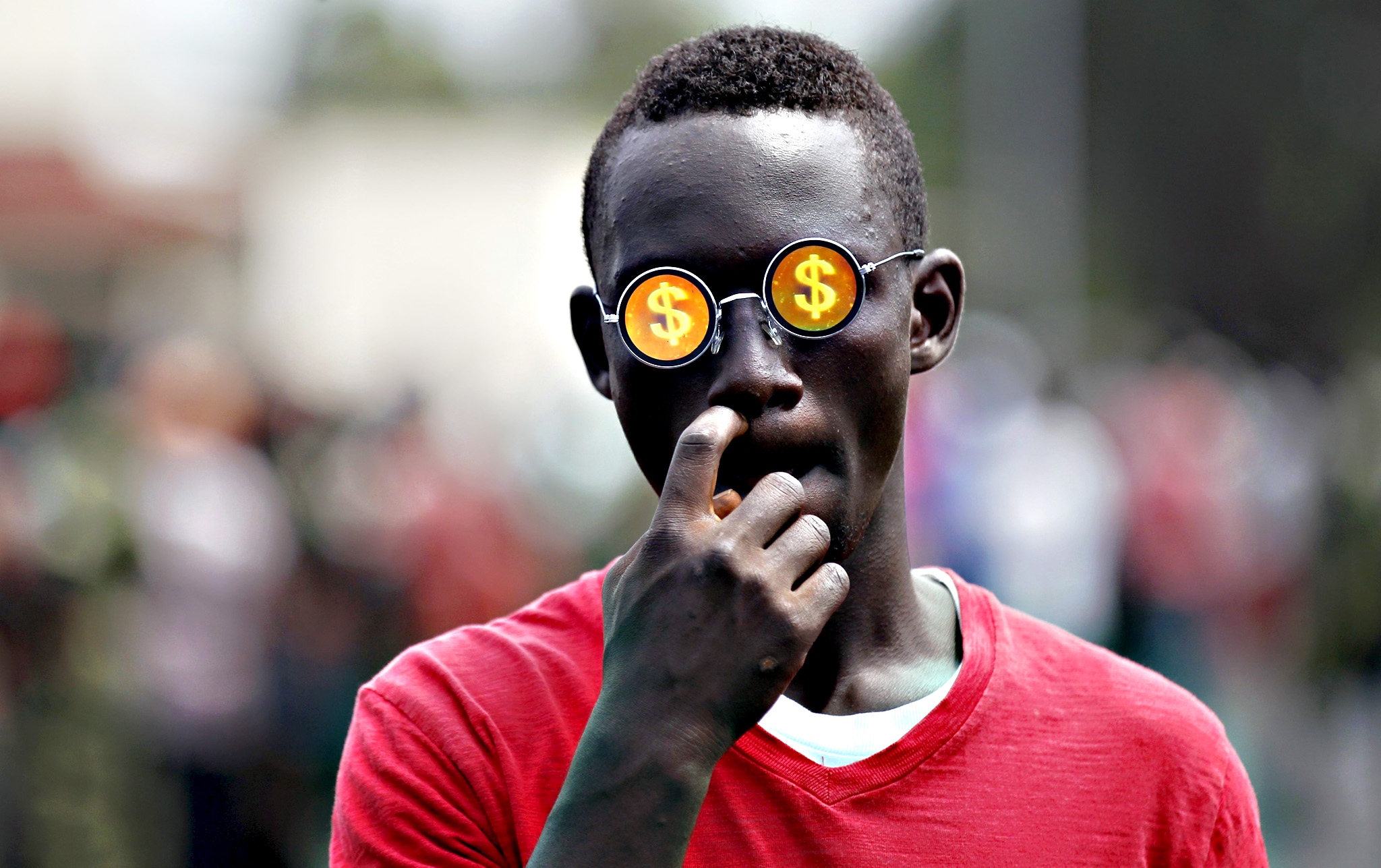 A boy wears sunglasses with the dollar sign as he walks down a street in Bujumbura, Burundi April 29, 2015.
