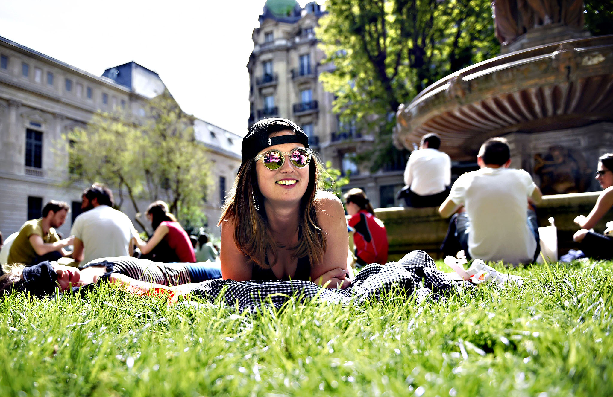 People relax in the sun in the gardens of the Palais Royal in Paris on April 15, 2015.
