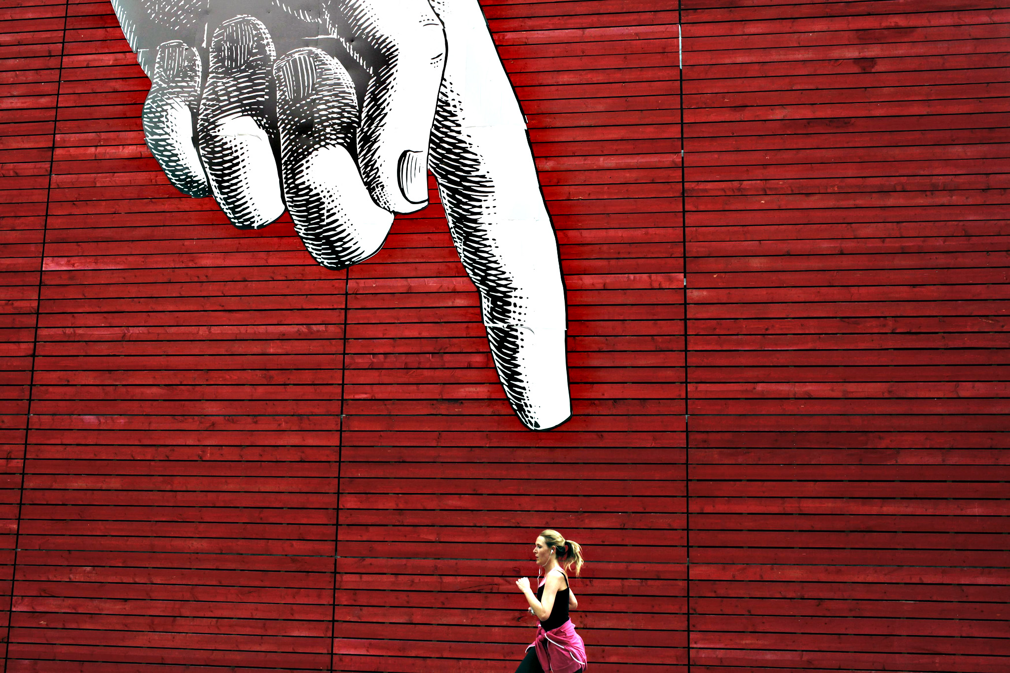 A woman runs past artwork of a large hand on a wall in central London, Britain on Monday