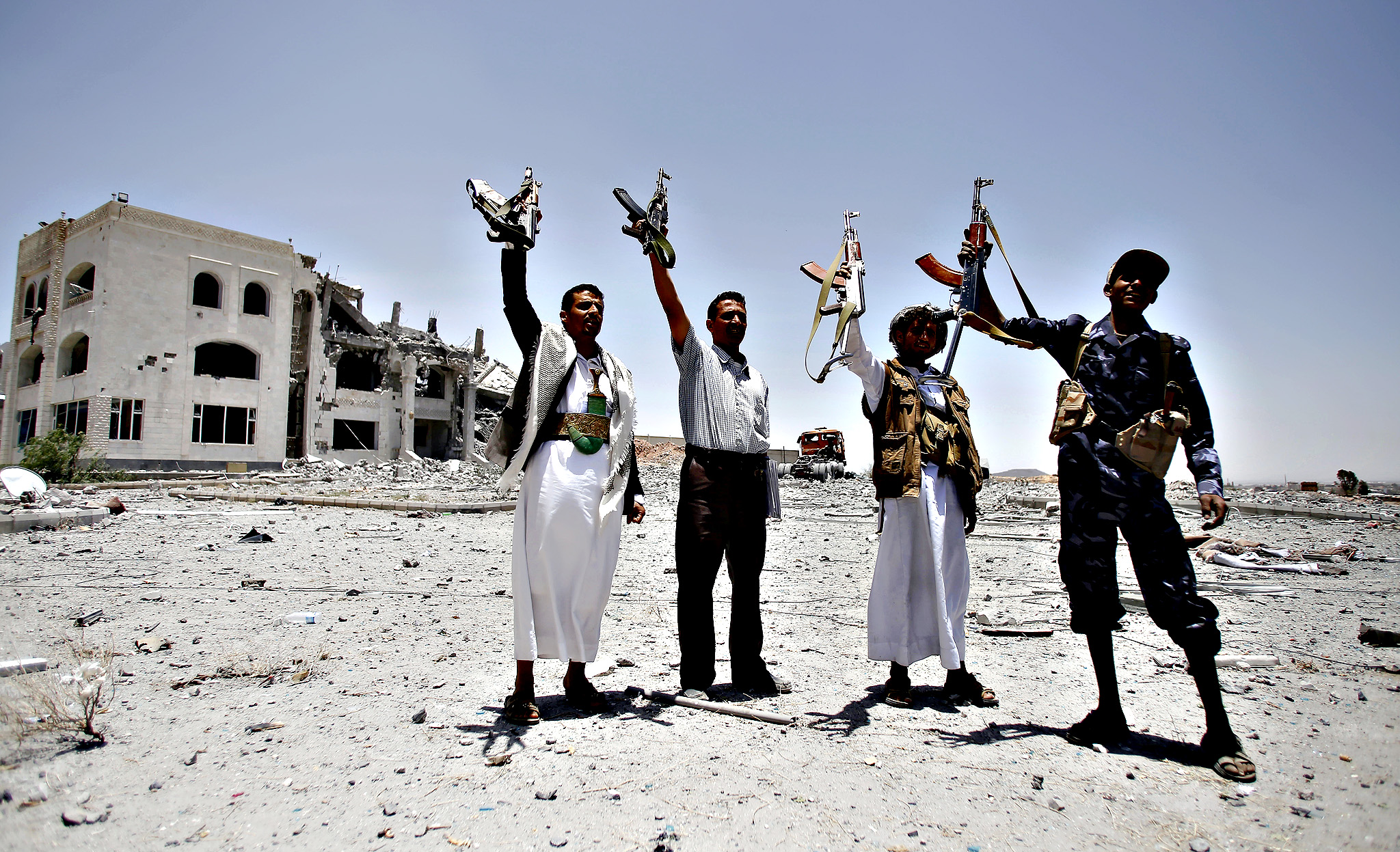 Shiite fighters, known as Houthis, hold up their weapons as they chant slogans at the residence of a military commander of the Houthi militant group, destroyed by a Saudi-led airstrike in Sanaa,, Yemen, Tuesday, April 28, 2015. A security official in Saudi Arabia says a soldier has been killed and another wounded in a gunfight with Shiite Houthi rebels along the kingdom's southern border with Yemen