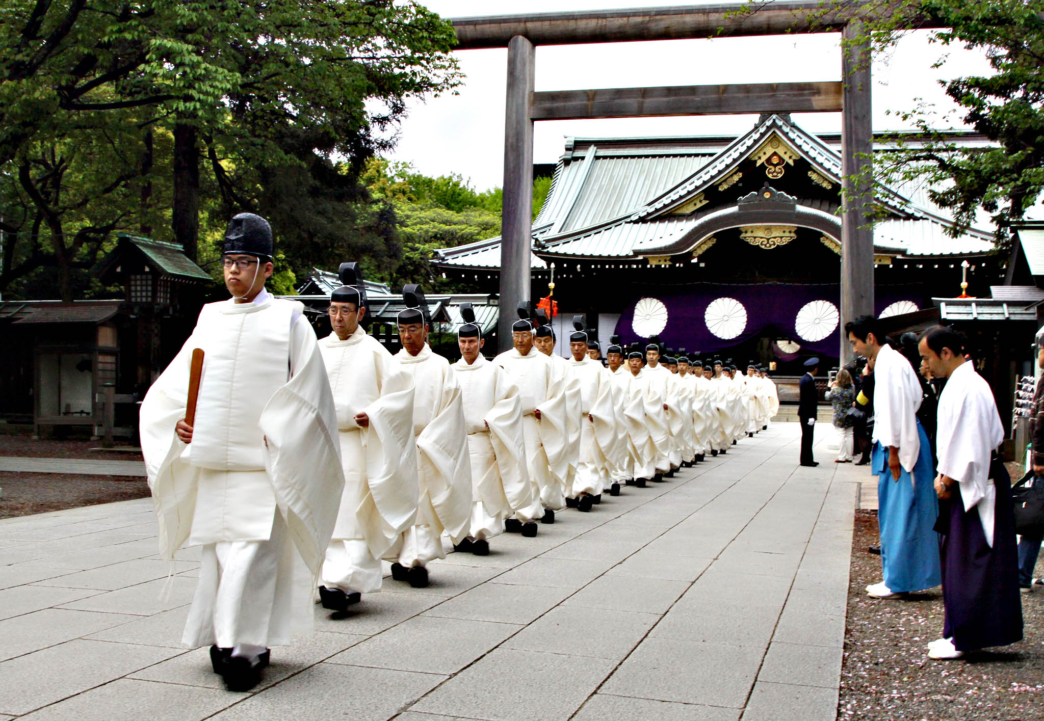 "Shinto priests walk out from a gate after they administered a Shinto rite ""Kiyoharai"" on the first day of the three-day spring festival at the controversial Yasukuni shrine in Tokyo on April 21, 2015. Japanese Prime Minister Shinzo Abe made a symbolic donation to the Yasukuni war shrine, but stopped short of visiting in person -- a move that would have infuriated neighbouring countries. Abe donated a sacred ""masakaki"" tree to coincide with the start of the three-day spring festival at the shrine in central Tokyo"