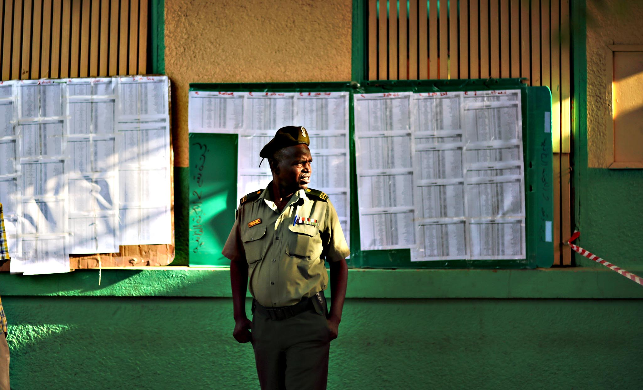 A member of the Sudanese security forces waits outside a polling station where he is registered to vote, in Khartoum, Sudan, Monday, April 13, 2015.