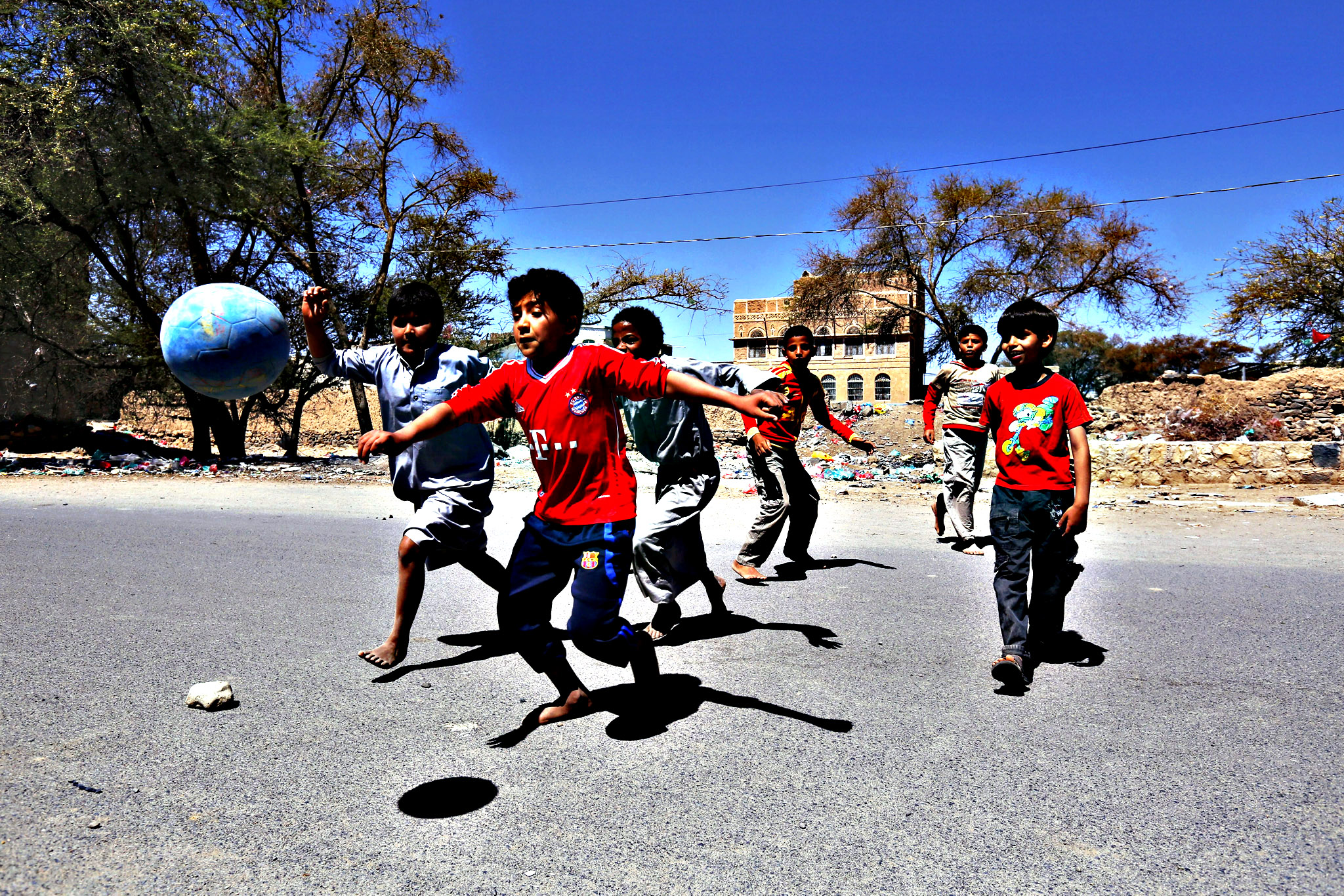 Young Yemenis play football on a street in Sanaa, Yemen on Thursday. Schools and universities have remained closed in Sanaa and several Yemeni cities since the Saudi-led coalition began its military operations on positions held by the Houthis and their allies across the country