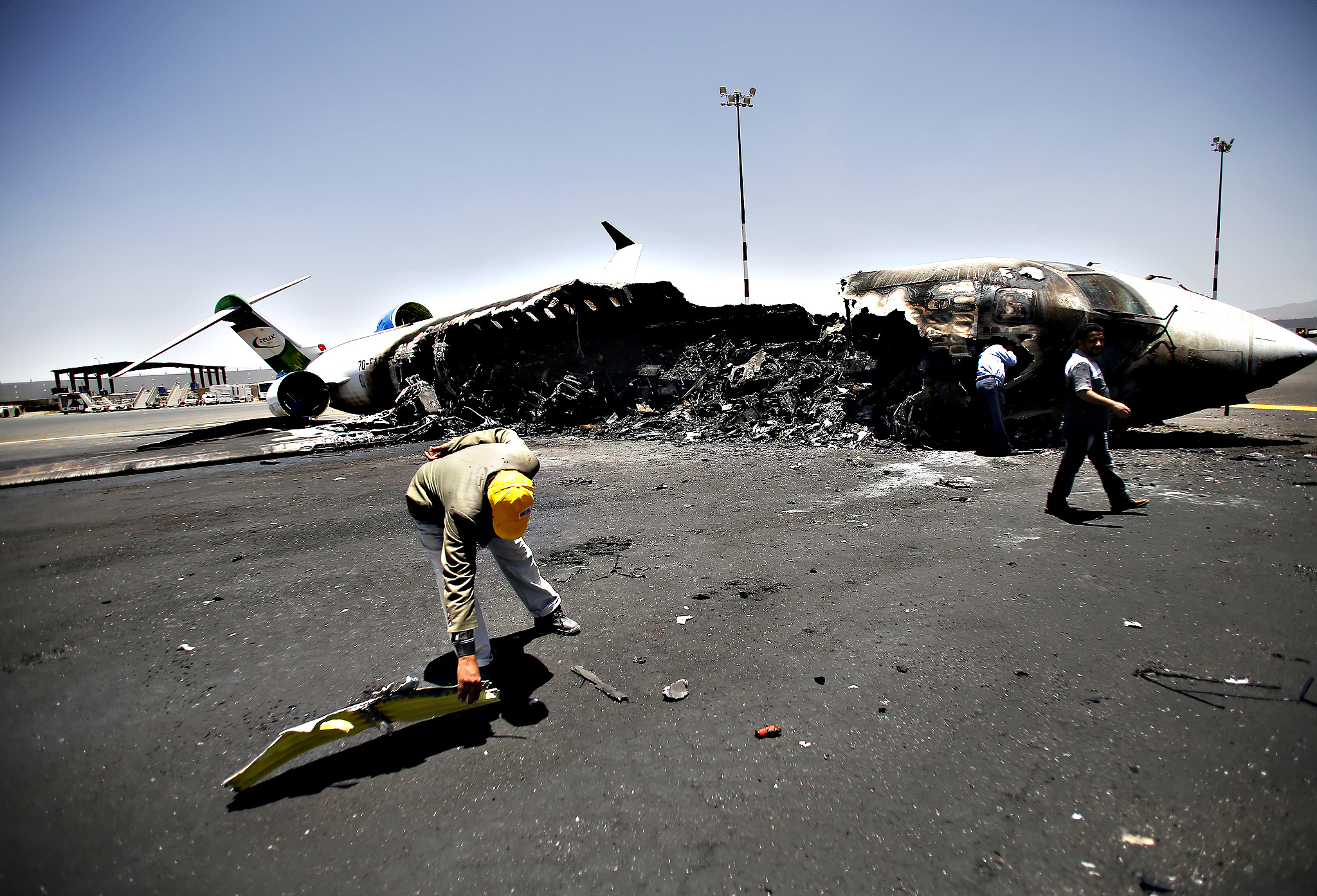 Officials of Felix Airways, a domestic airline, inspect a plane destroyed by Saudi-led airstrikes, at the Sanaa International airport, in Yemen, Wednesday, April 29, 2015. Saudi-led coalition warplanes pounded Shiite rebels and their allies overnight and throughout the day on Tuesday in the Yemeni capital. Around midday, airstrikes hit Sanaa International airport, setting a plane owned by a private company on fire, according to a statement released by the Shiite rebels, known as Houthis