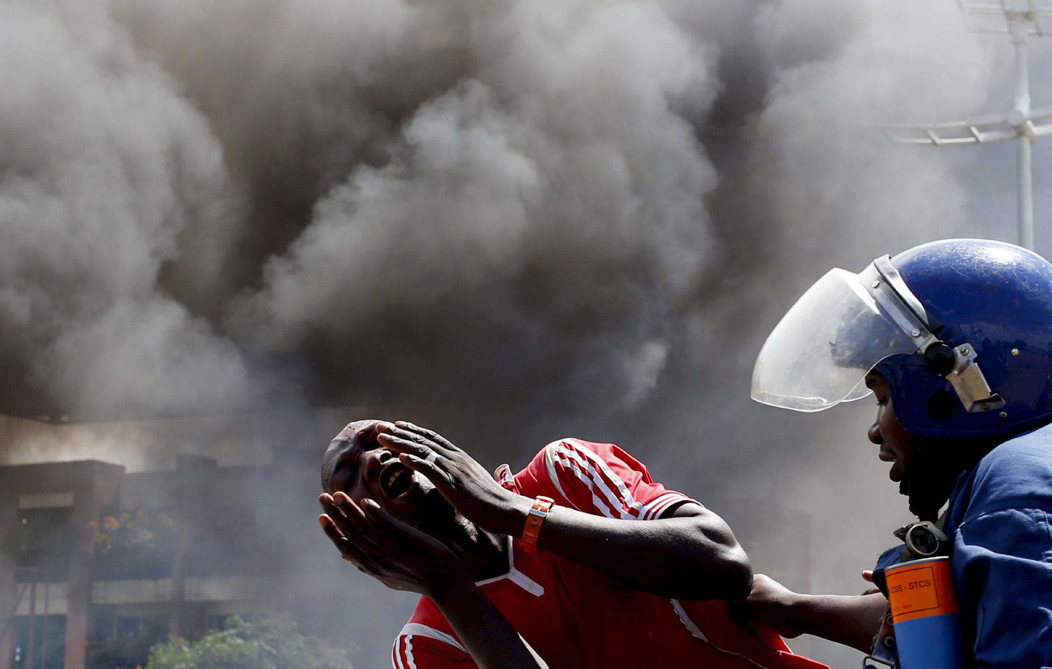 A detained protester cries in front of a burning barricade during a protest against President Pierre Nkurunziza's decision to run for a third term in Bujumbura, Burundi May 13, 2015.