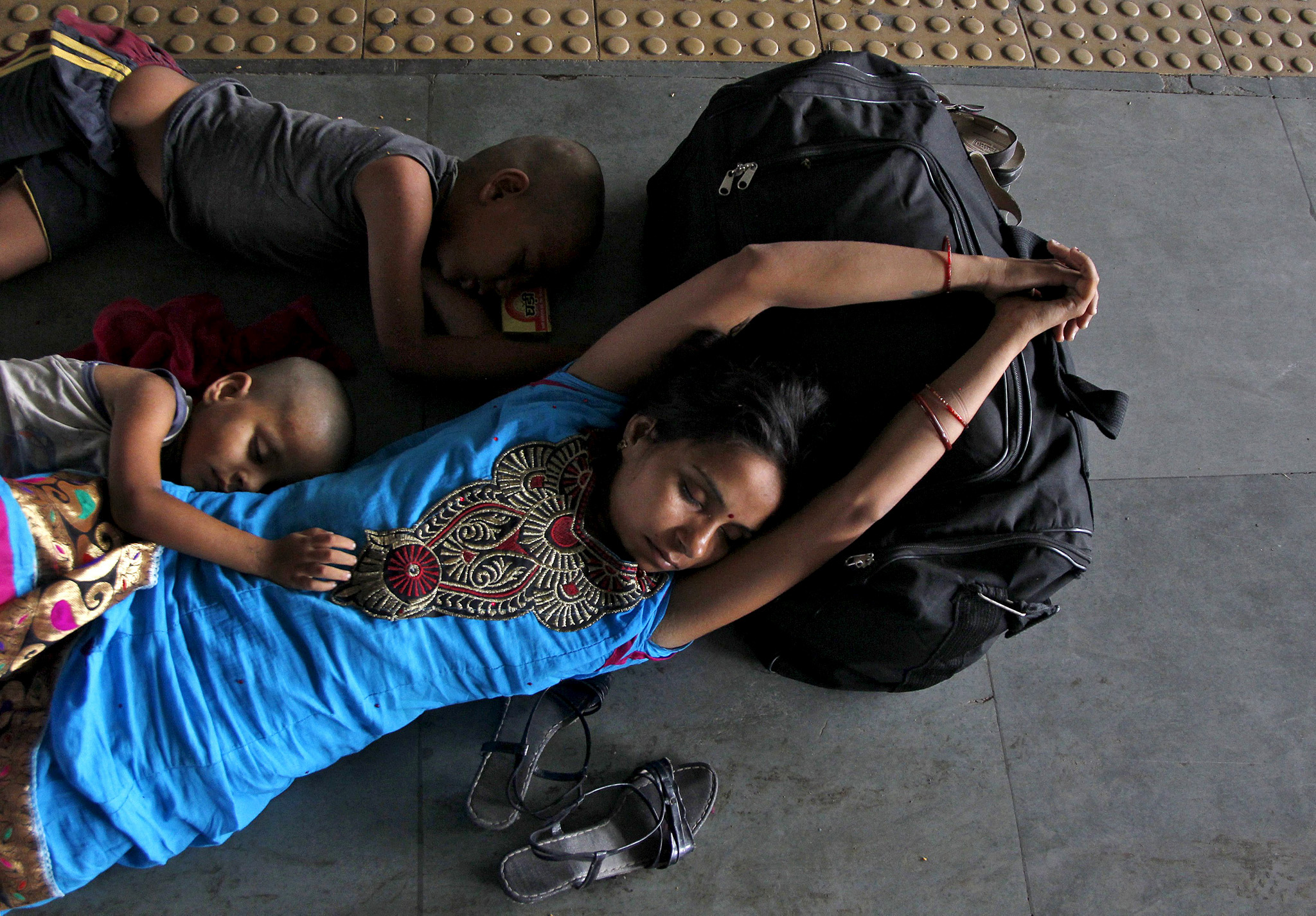 A passenger sleeps along with her children at a railway station on a hot summer day in Allahabad...A passenger sleeps along with her children at a railway station on a hot summer day in Allahabad, India, May 26, 2015. Temperature in Allahabad on Tuesday is expected to reach 46.4 degree Celsius (115.5 degree Fahrenheit), according to India's metrological department website. REUTERS/Jitendra Prakash      TPX IMAGES OF THE DAY