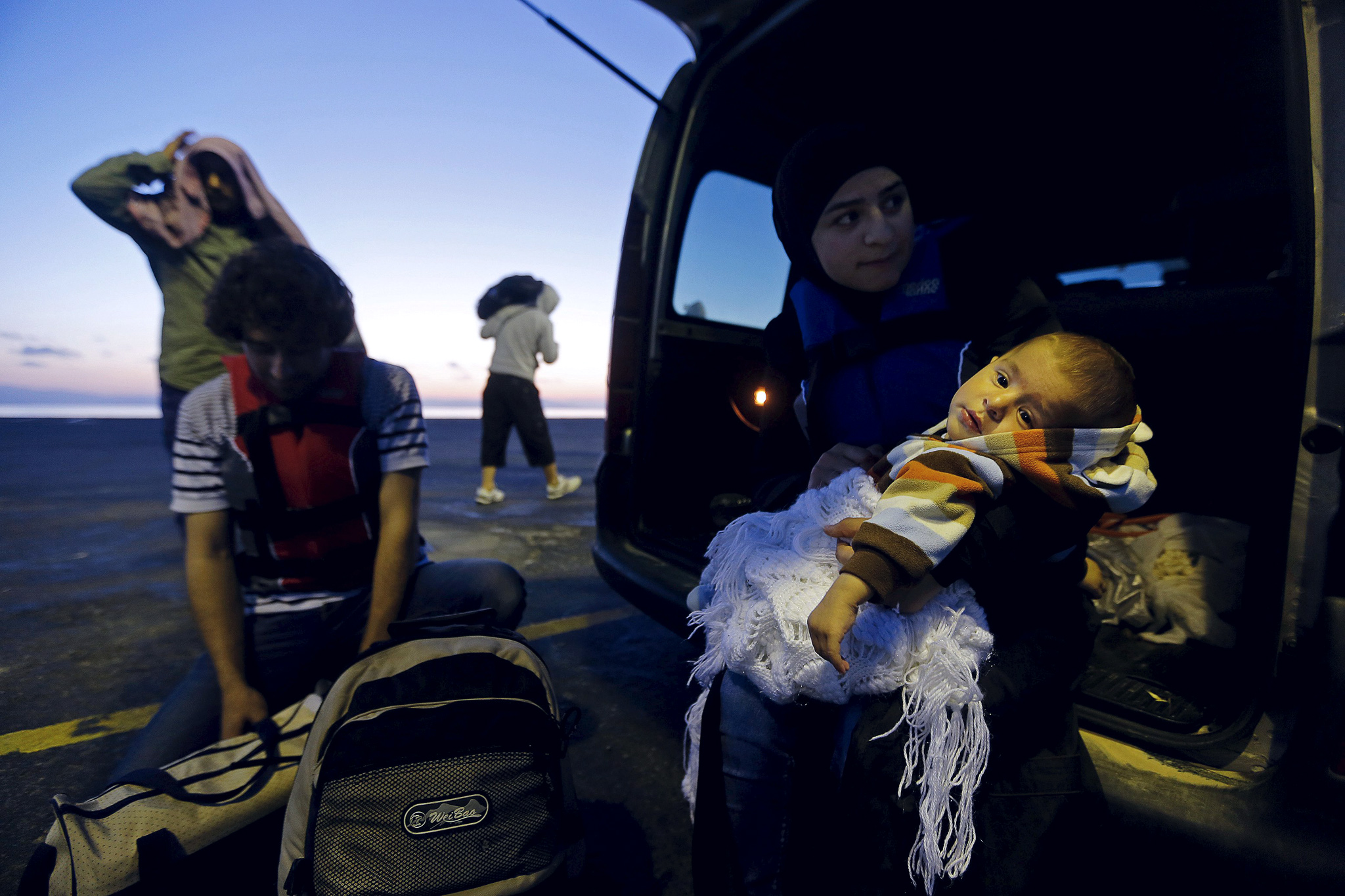 Syrian refugees are seen on Kos following an attempt to cross part of the Aegean Sea from Turkey to Greece...REFILE CORRECTIN GRAMMAR Seven-month-old Syrian refugee Jaffe is held by her mother Nada in a Greek coast guard van next to her father Ahmed (L), after they were rescued, on the Greek island of Kos following an attempt to cross part of the Aegean Sea from Turkey to Greece early May 26, 2015. Hundreds of mainly Syrian and Afghan immigrants on Tuesday landed on the Greek island of Kos in the south-eastern Aegean Sea. REUTERS/Yannis Behrakis