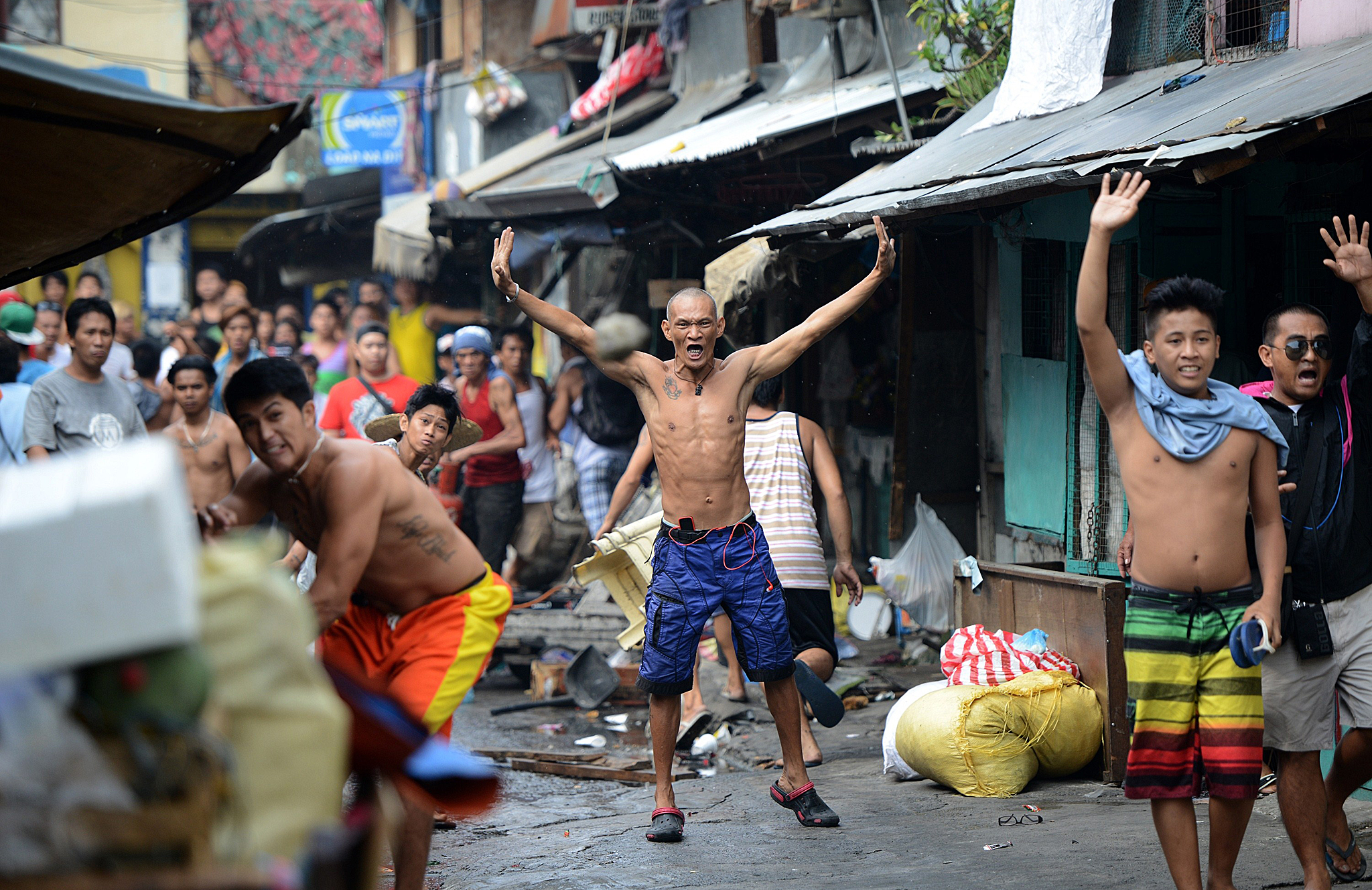 TOPSHOTS A resident (front L) throws an ...TOPSHOTS A resident (front L) throws an empty bottle (C) towards advancing policemen and a demolition team during the demolition of an informal settlers community in Manila on May 26, 2015, to redevelop the area into a business district in a joint venture with a private firm. Some 500 families were affected by the demolition. AFP PHOTO / NOEL CELISNOEL CELIS/AFP/Getty Images